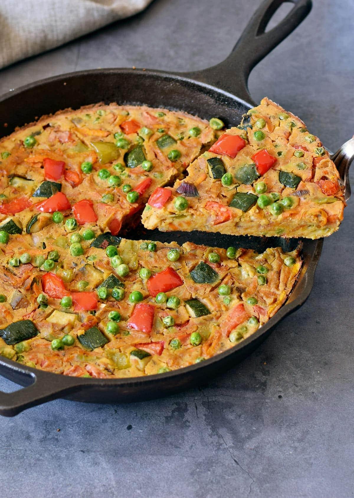 Veganes Gemüse Omelett wird aus schwarzer Pfanne herausgehoben