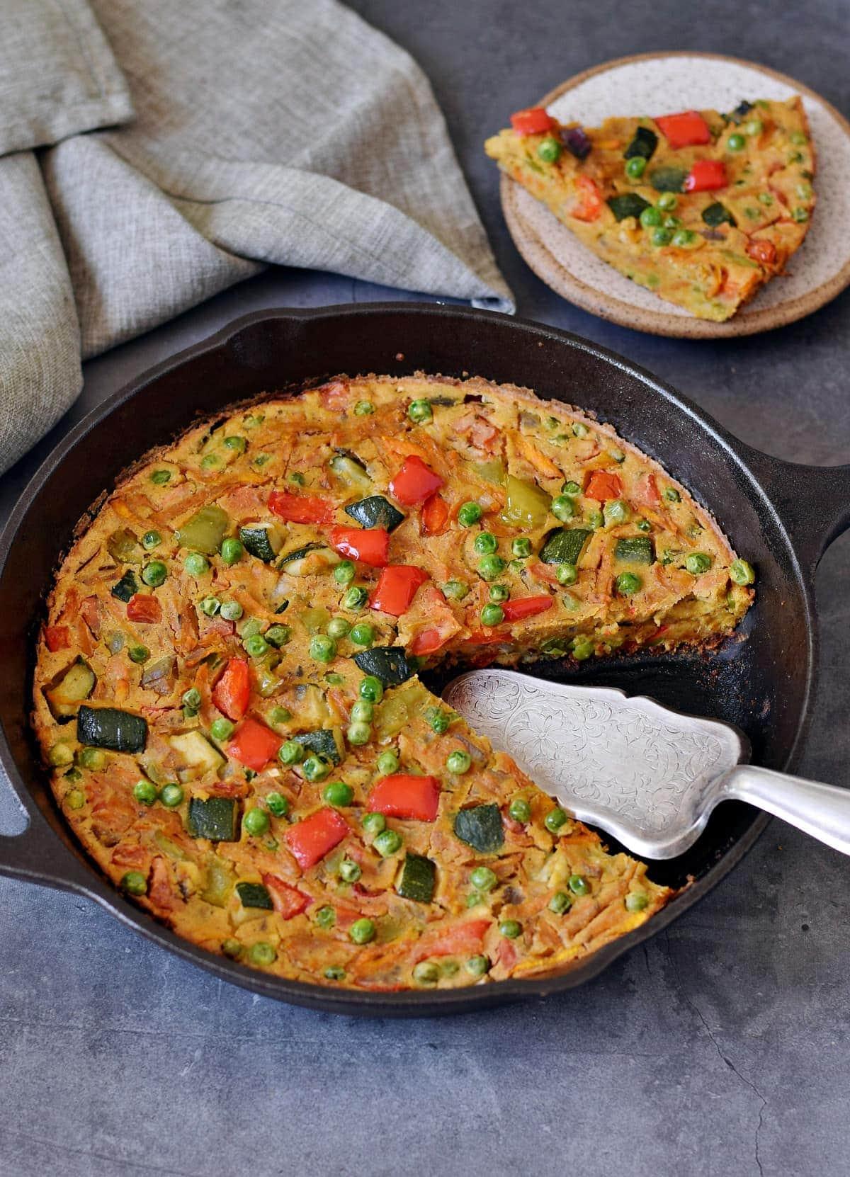Gemüse Frittata in Gusseisenpfanne mit Stück auf Teller