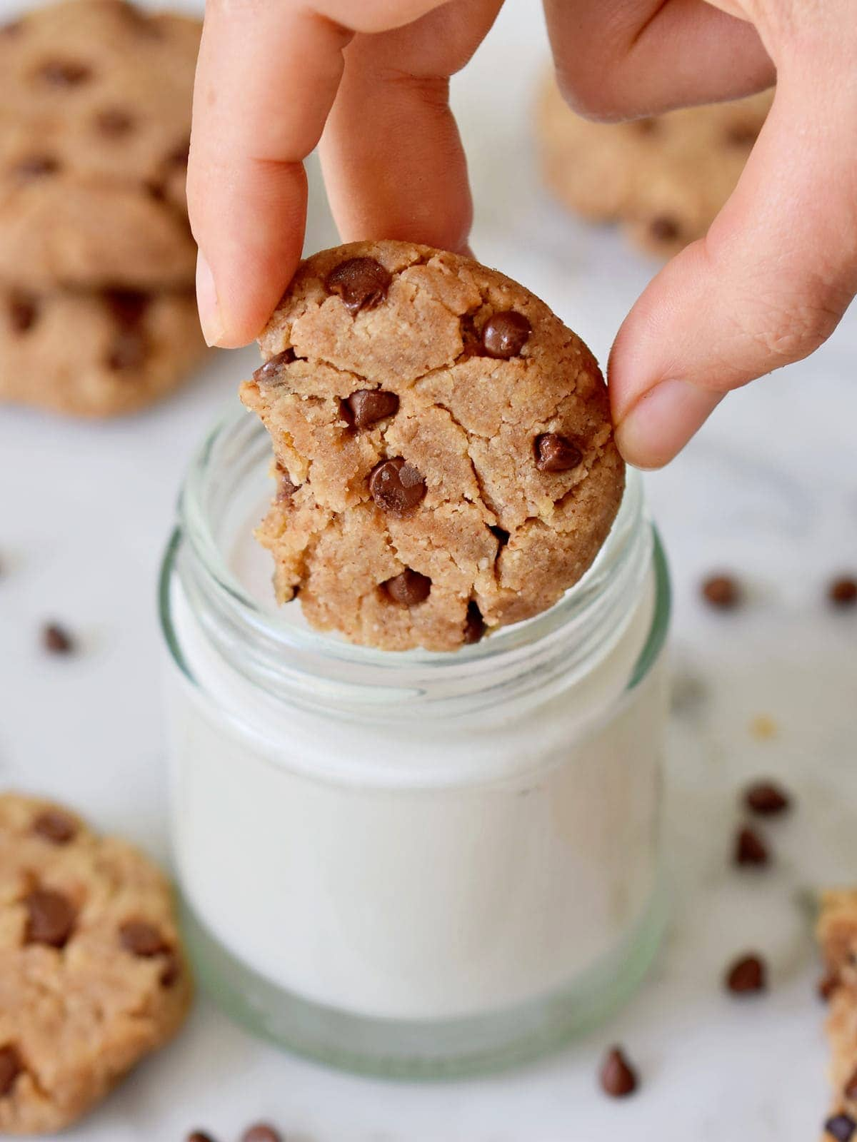 hand holding a cookie with chocolate chips over a glass of milk