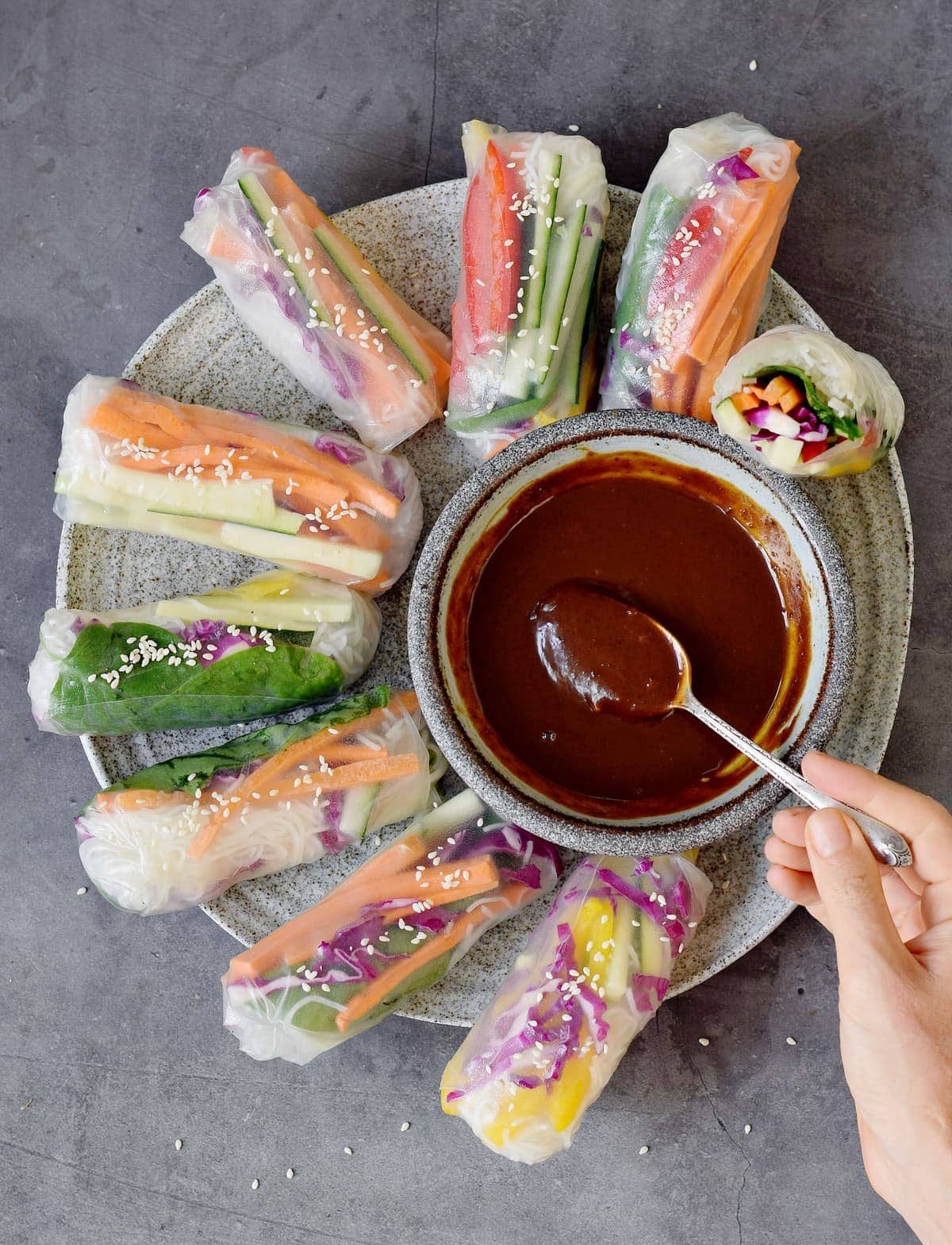 hand holds spoon submerged in hoisin sauce on a platter with summer rolls