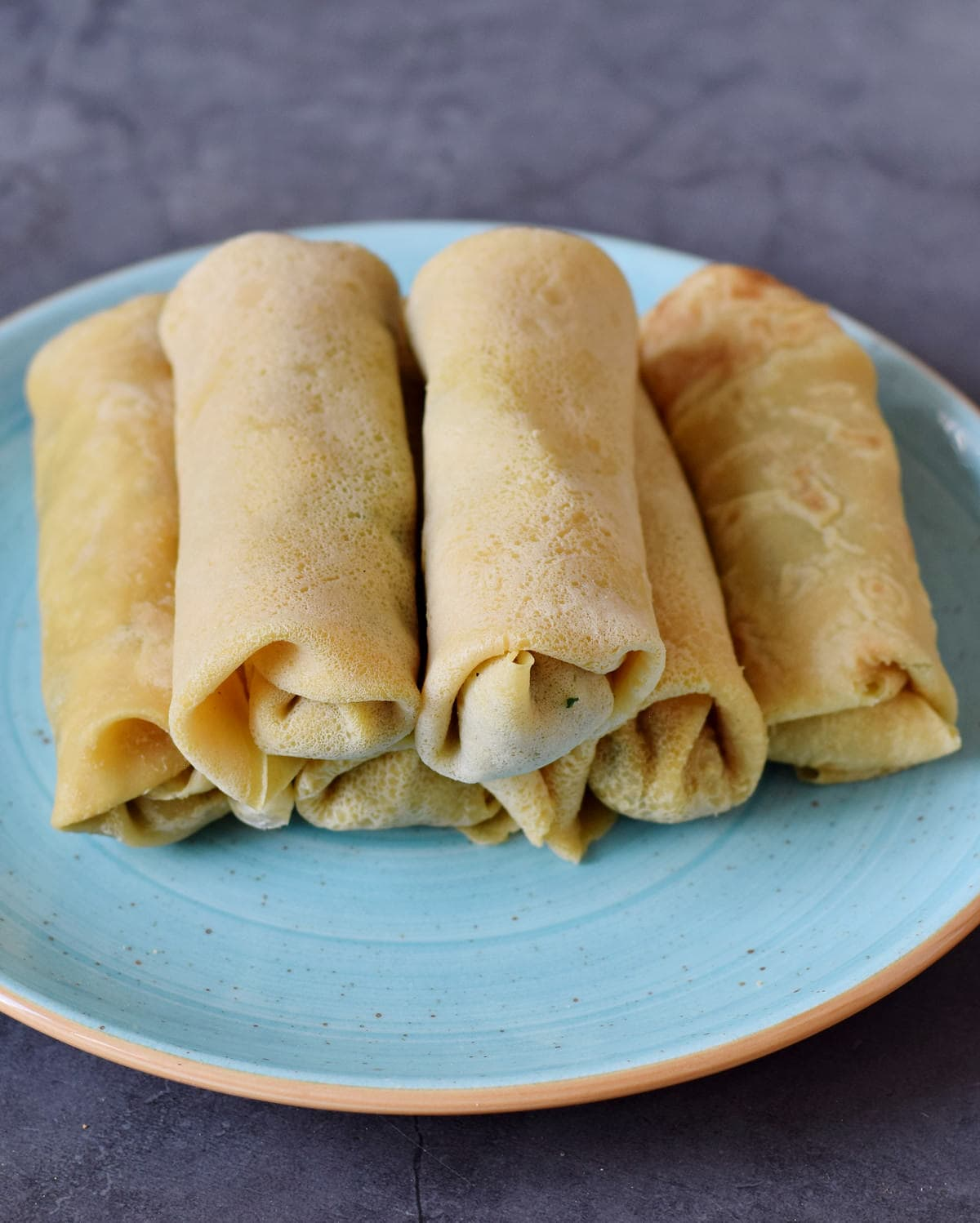 six rolled up stuffed hearty wraps on a turquoise plate
