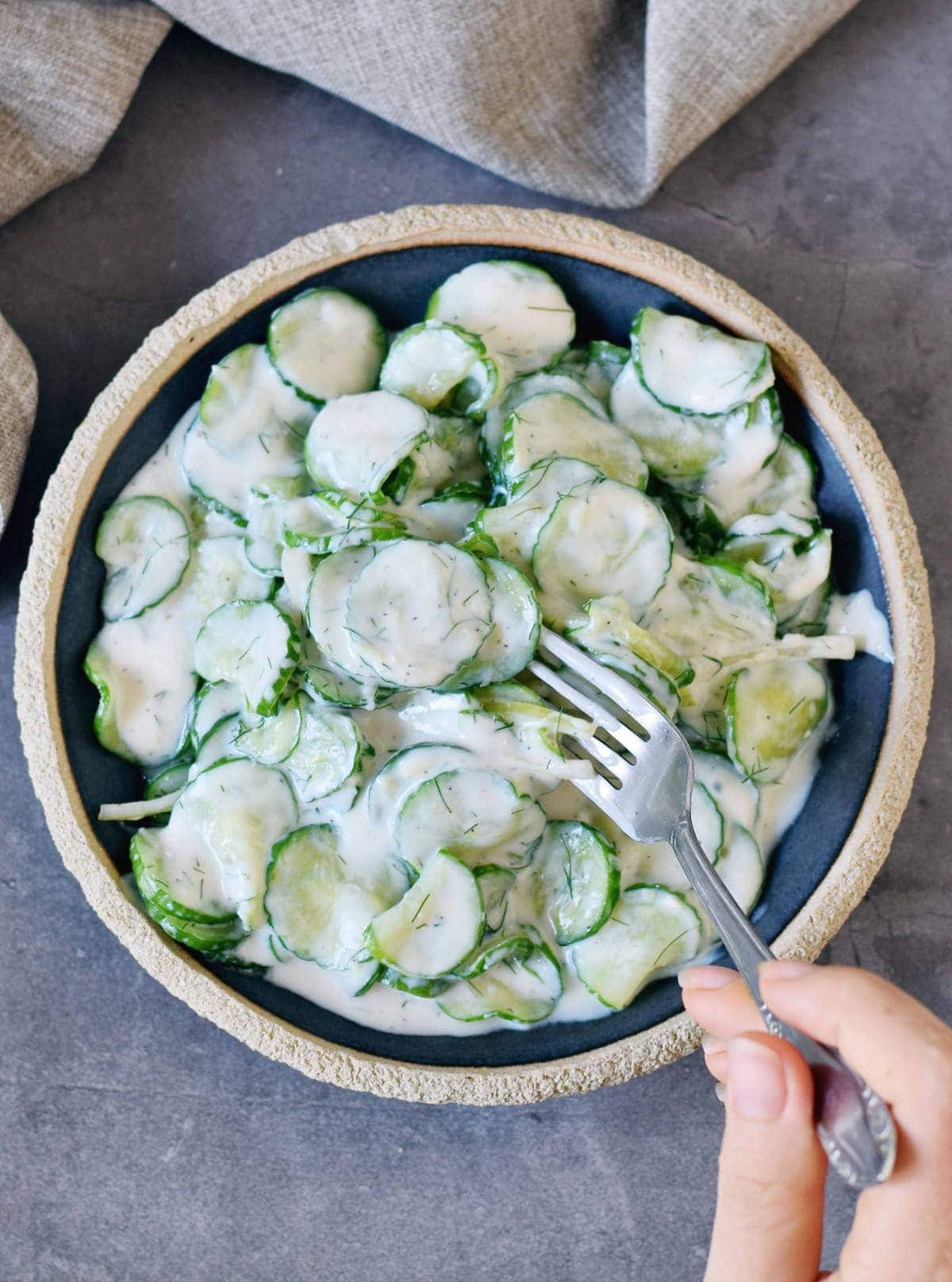 Hand holding fork submerged in creamy cucumber and onion salad