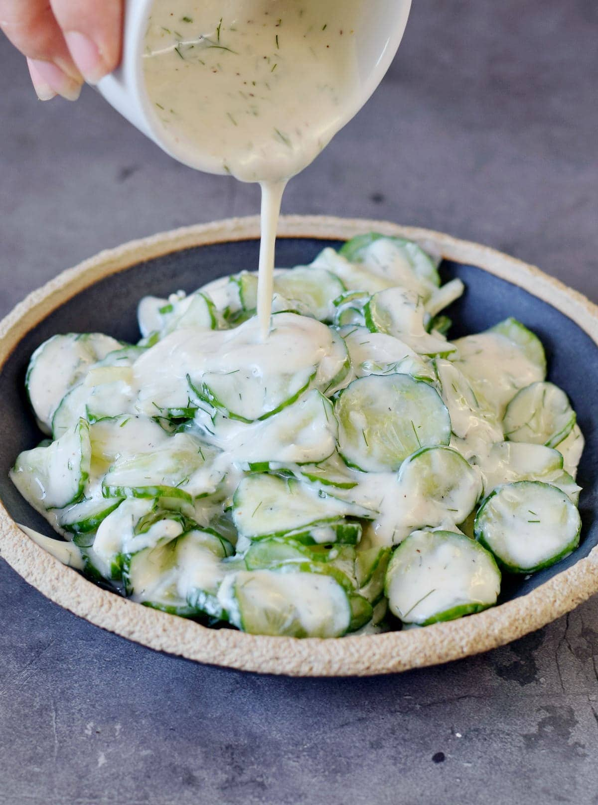 Pouring creamy dill dressing over German cucumber salad