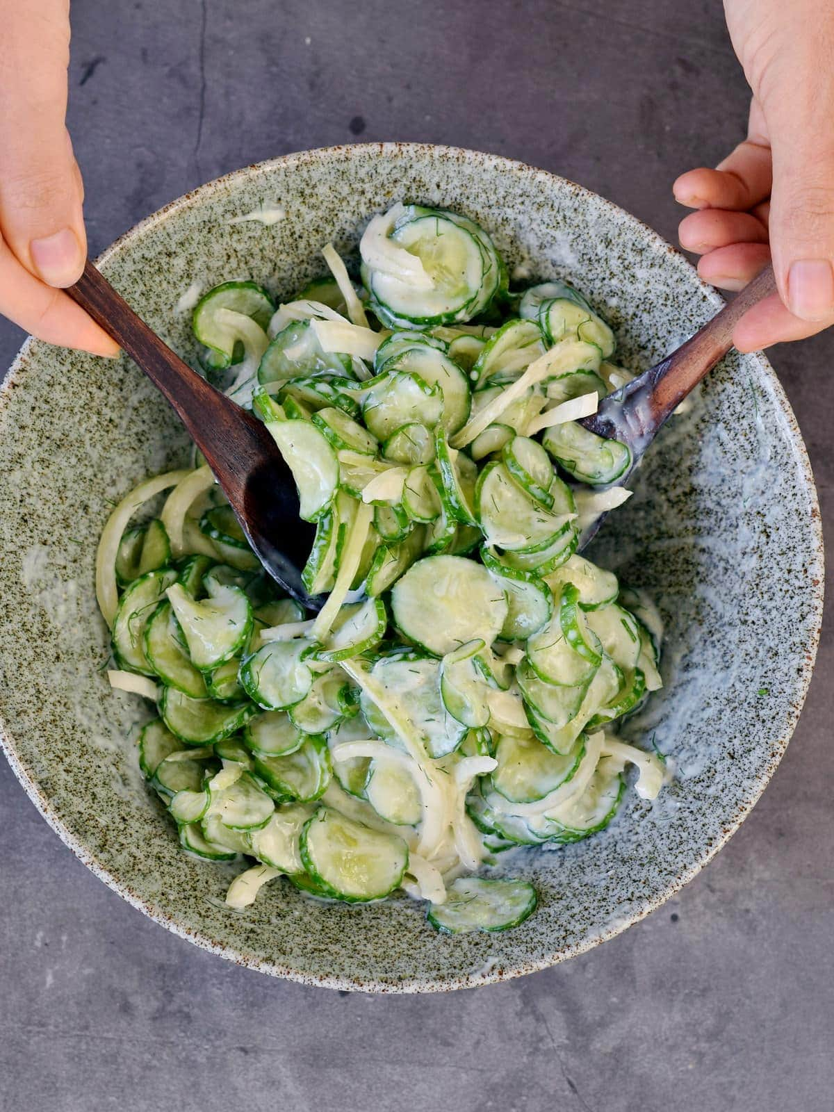 Stirring sliced cucumbers and dill dressing in a bowl