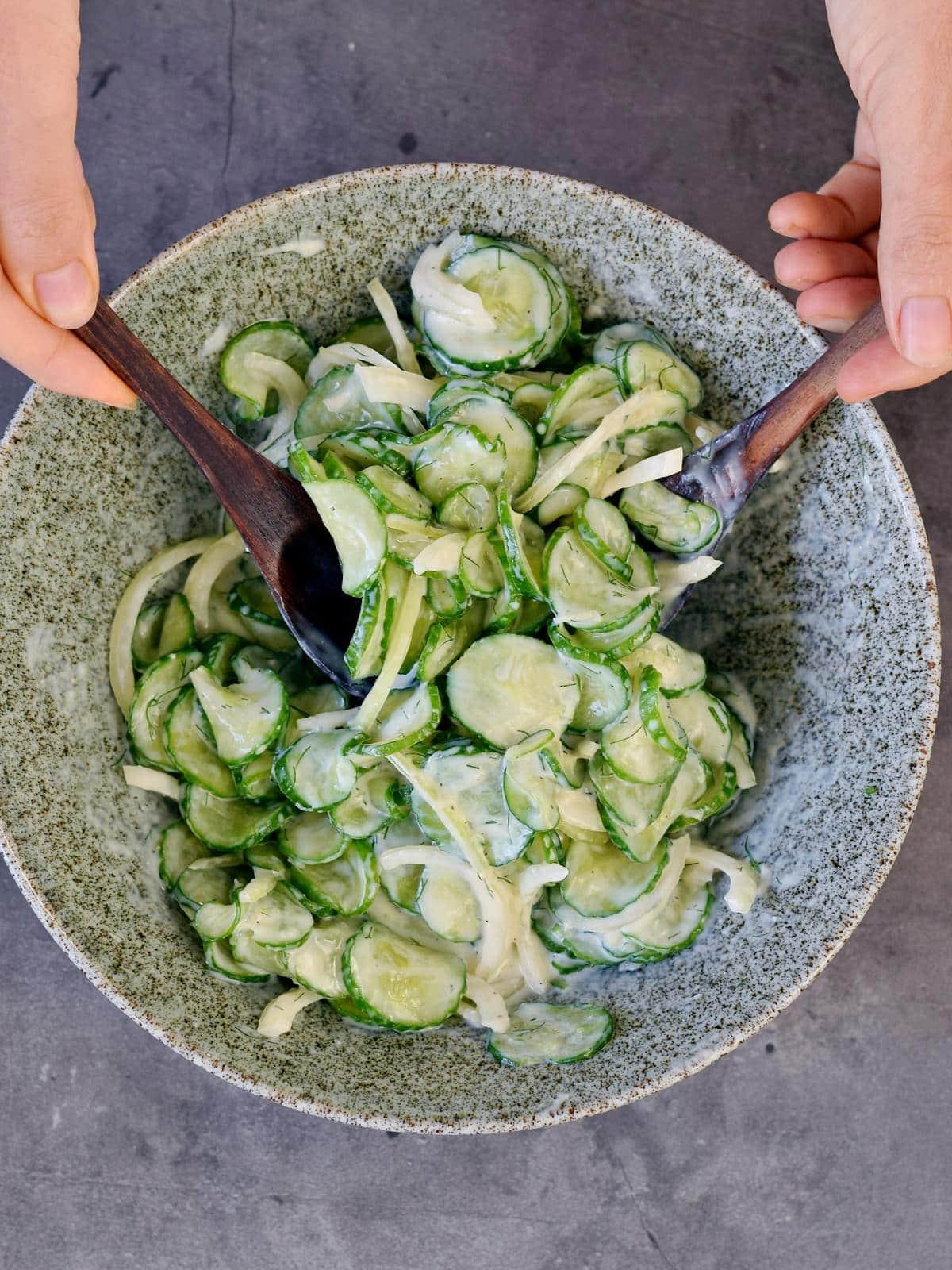 Salat mit Gurken wird mit zwei Löffeln in großer Schüssel verrührt