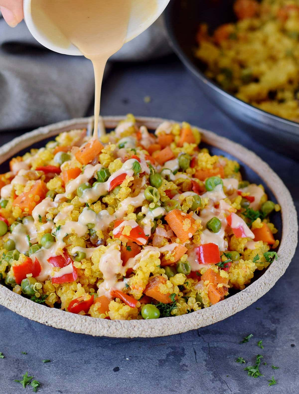 drizzling creamy salad dressing over quinoa pilaf