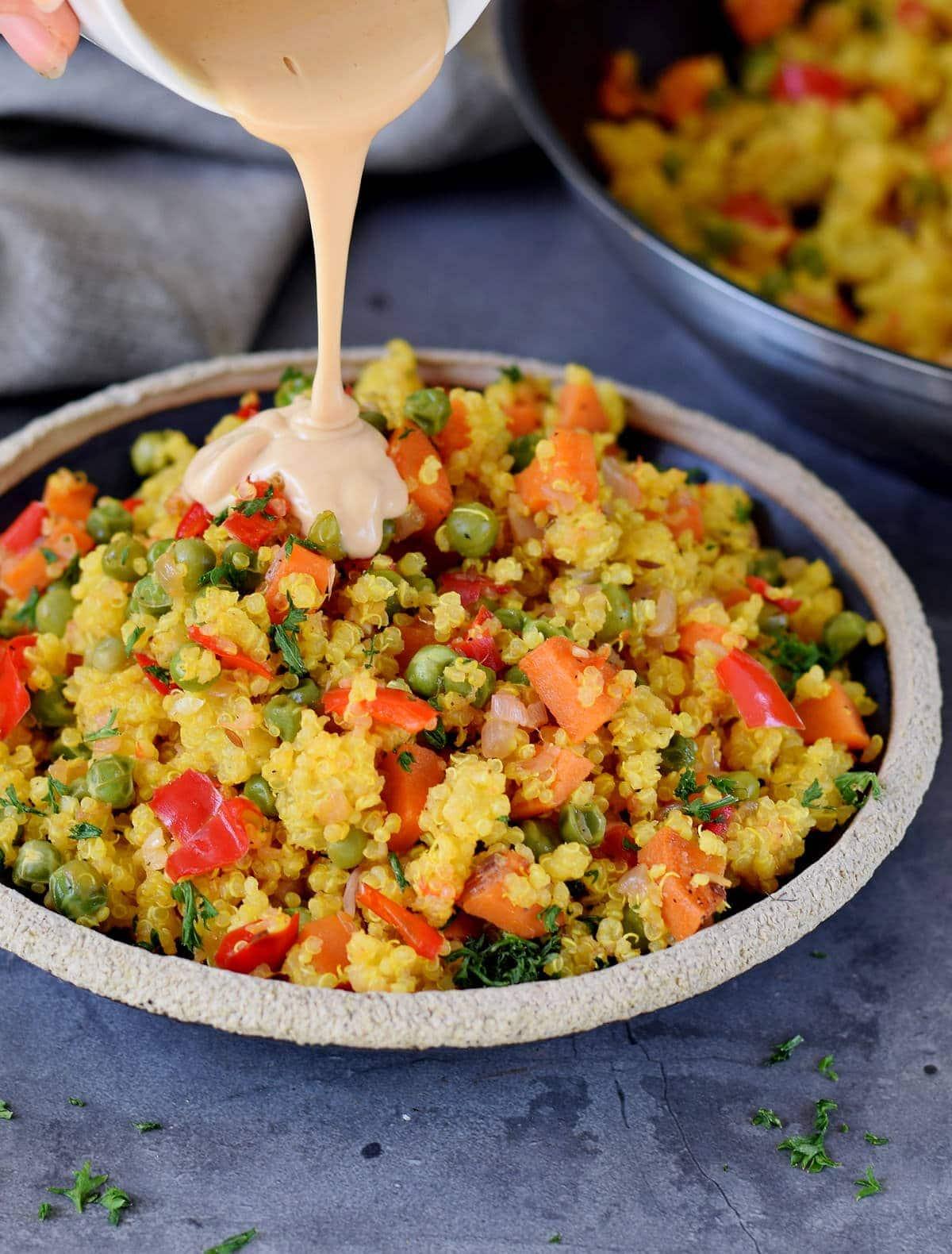 pouring salad dressing over quinoa veggie mixture