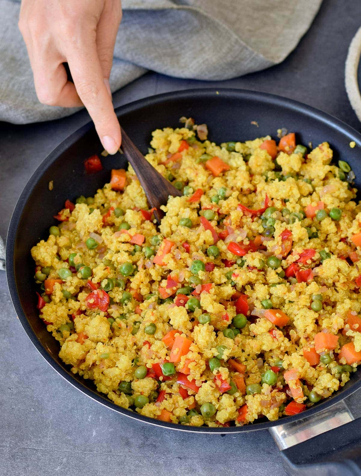 quinoa pilaf with veggies in a black pan