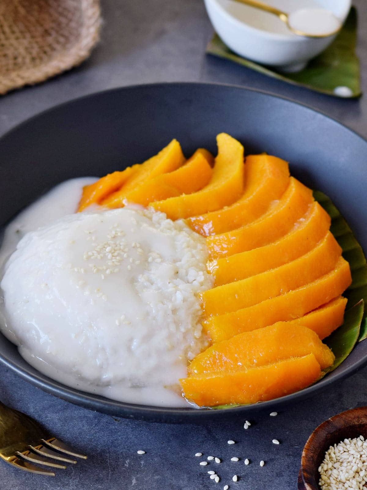 Close-up of Thai dessert with sliced mangoes in black bowl