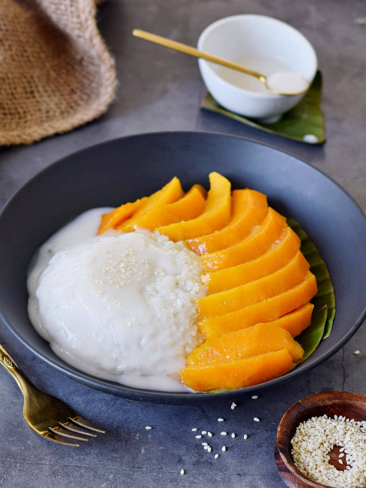 Glutinous rice with sliced mangoes in black bowl