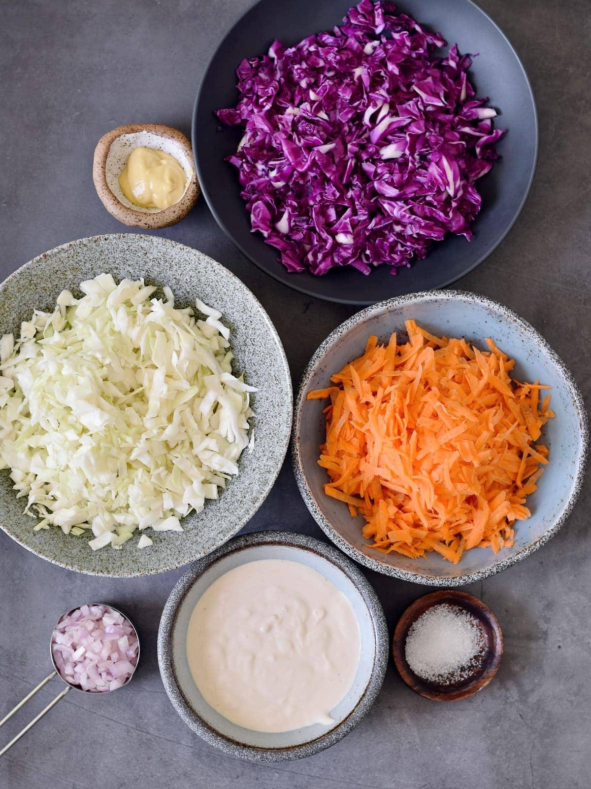 Kohl, veganer Sauerrahm und geriebene Karotten auf grauem Hintergrund