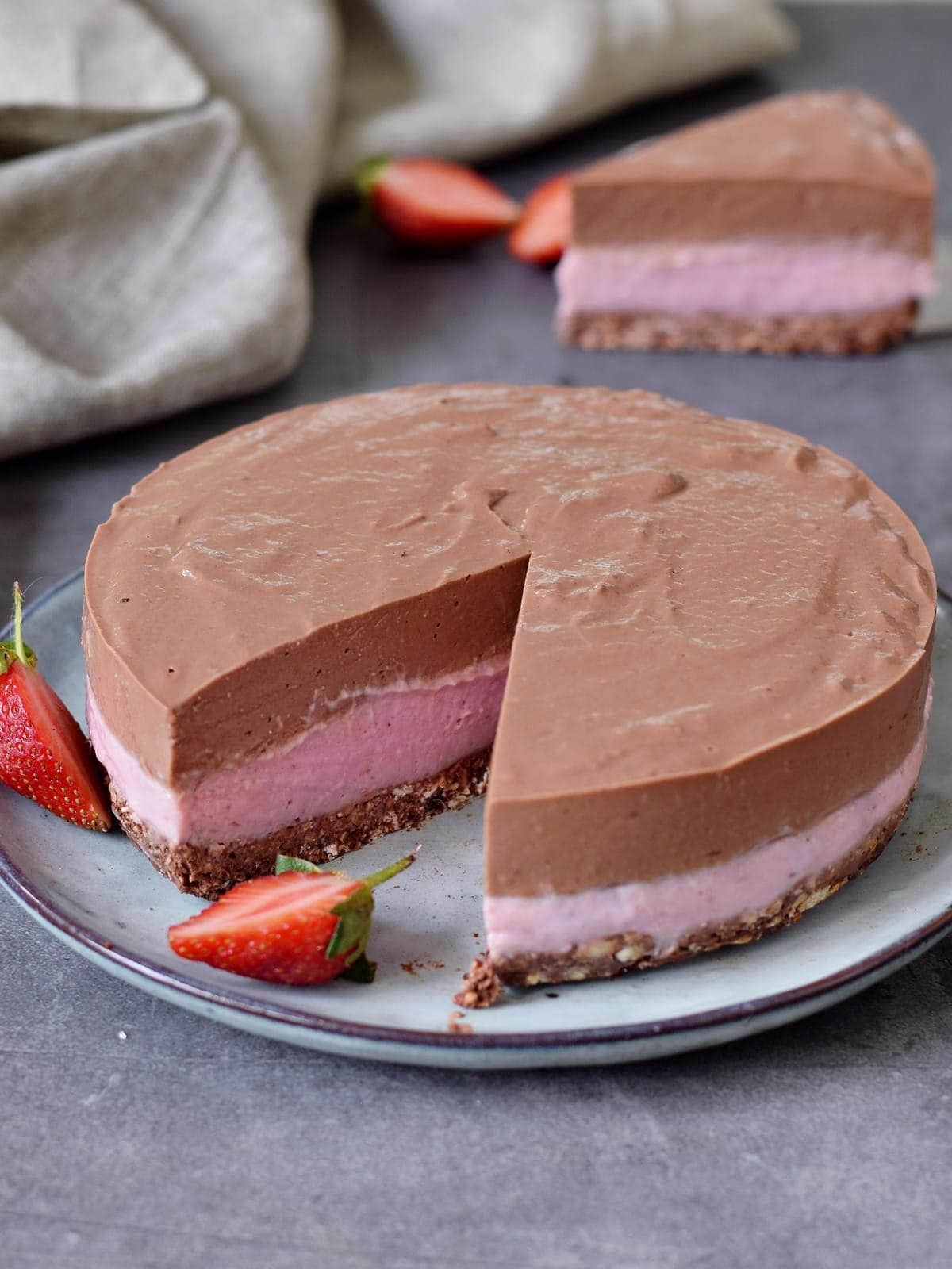 chocolate strawberry cheesecake with one piece in the background