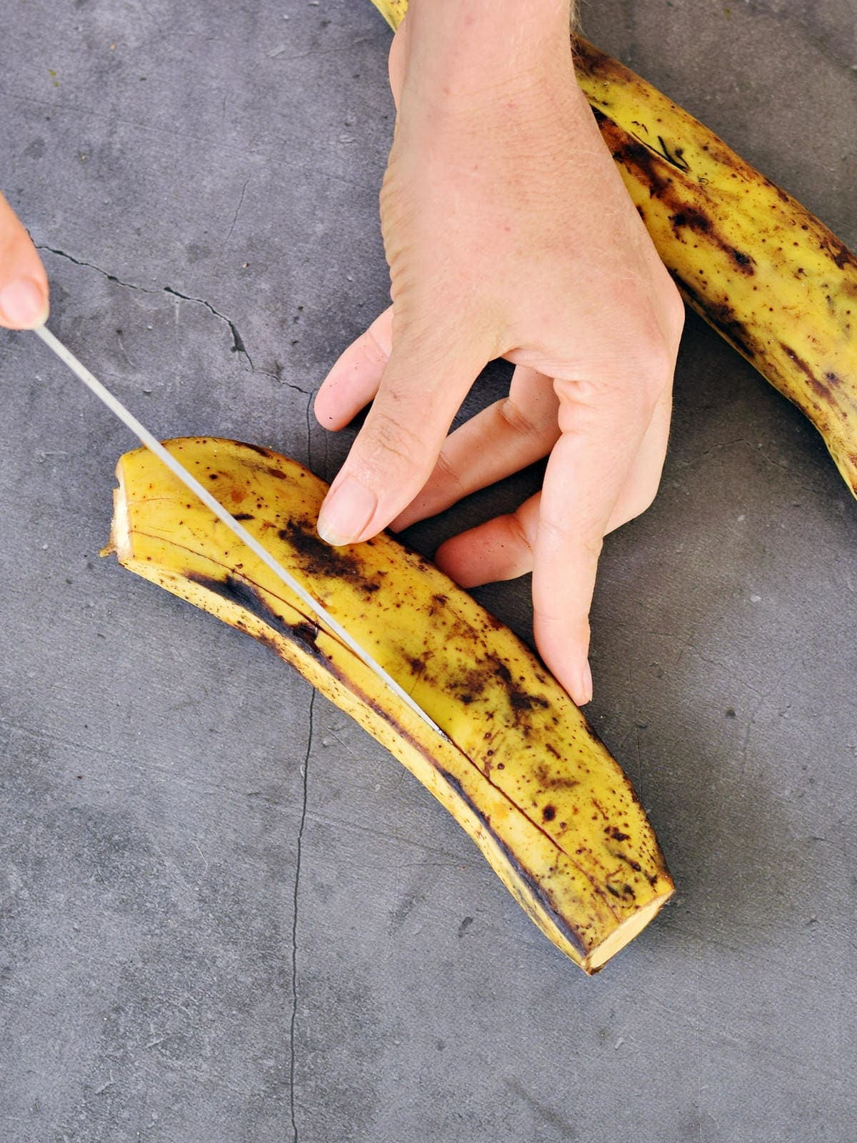 cutting into plantain skin with a knife