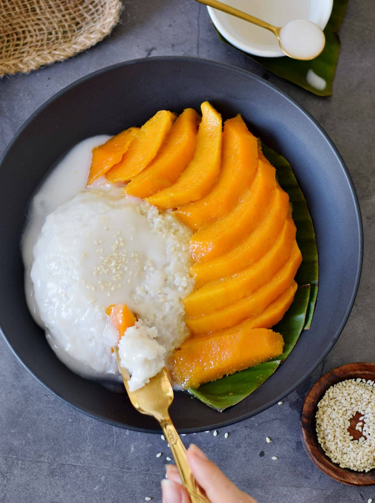 eating coconut milk rice with sliced mangoes