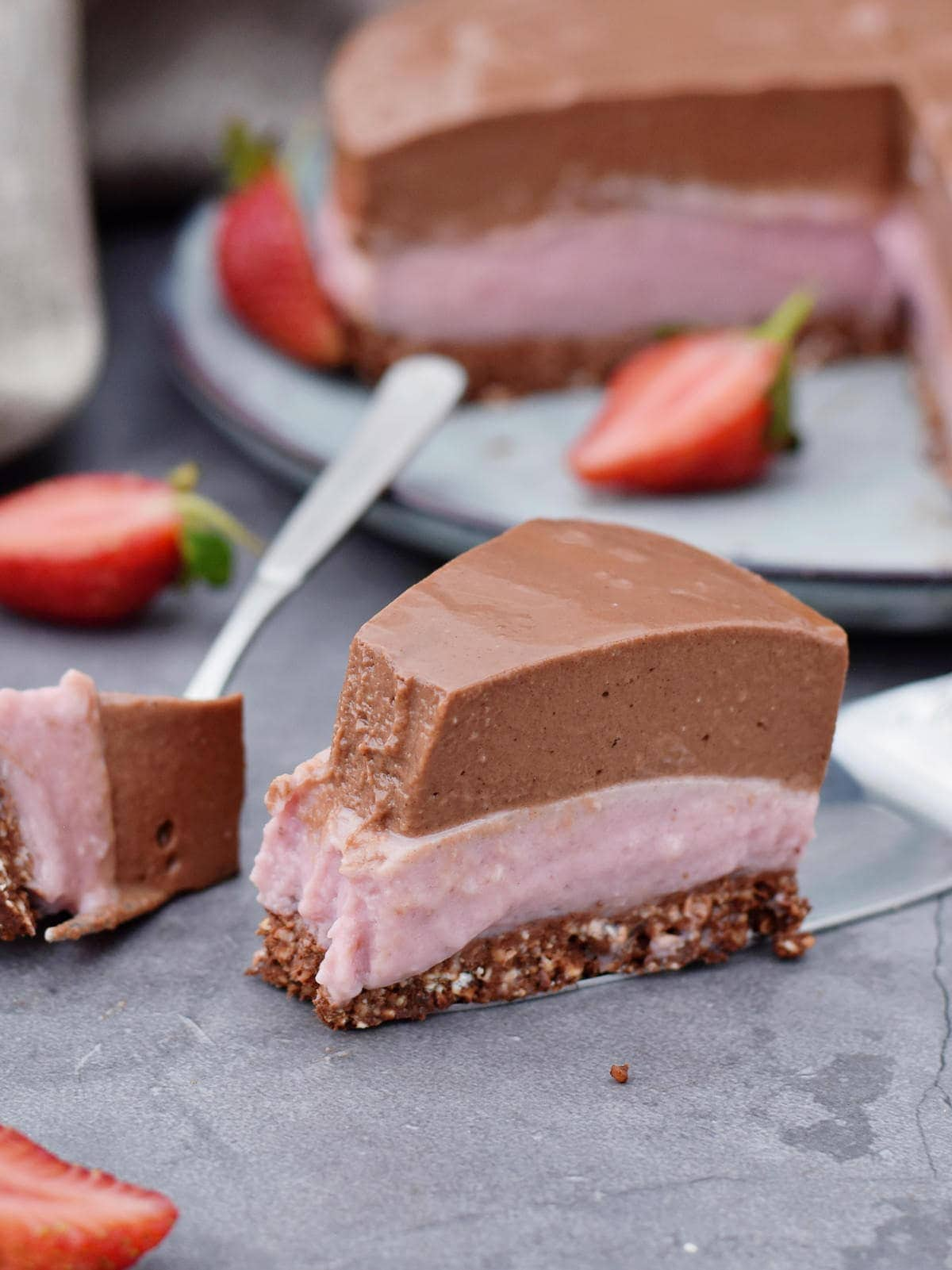 eating one piece of vegan chocolate strawberry cheesecake