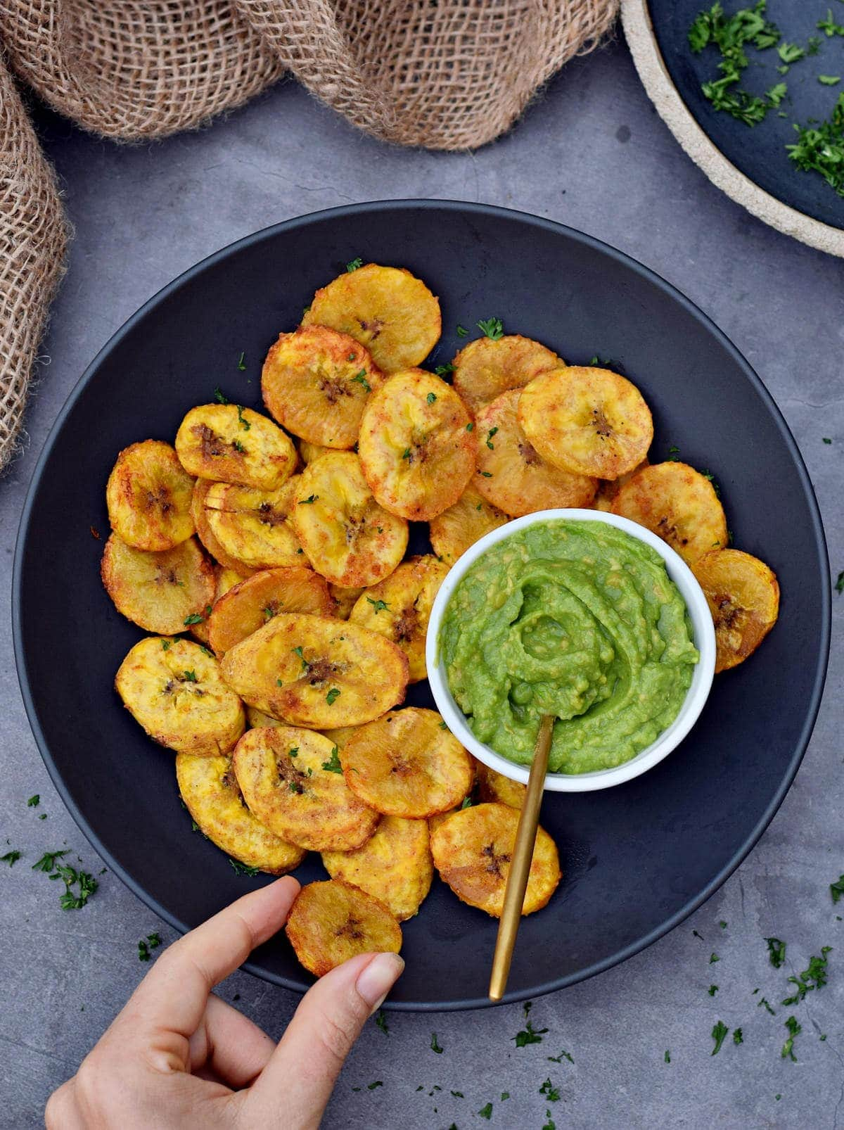 hand grabbing baked plantains in black bowl with guacamole dip