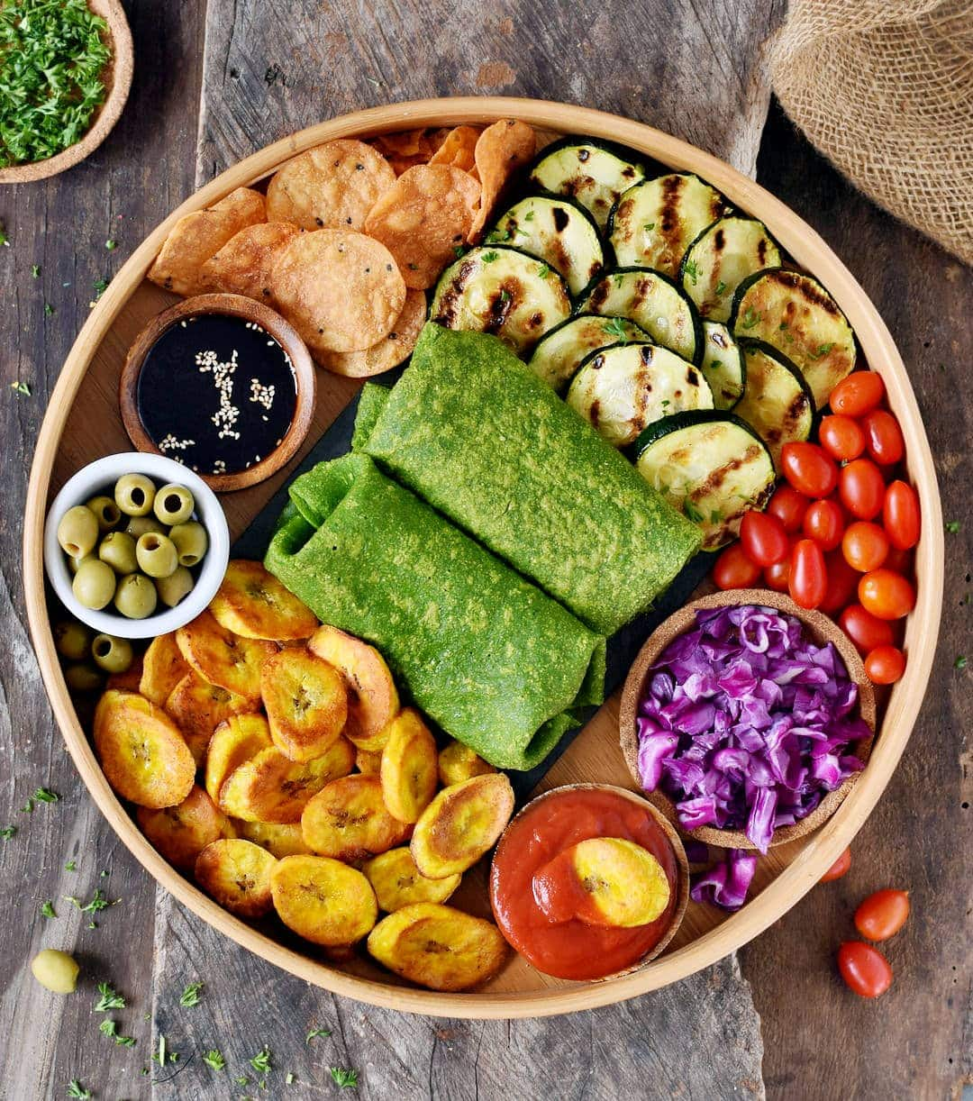 plantain chips with spinach wraps and veggies on a platter