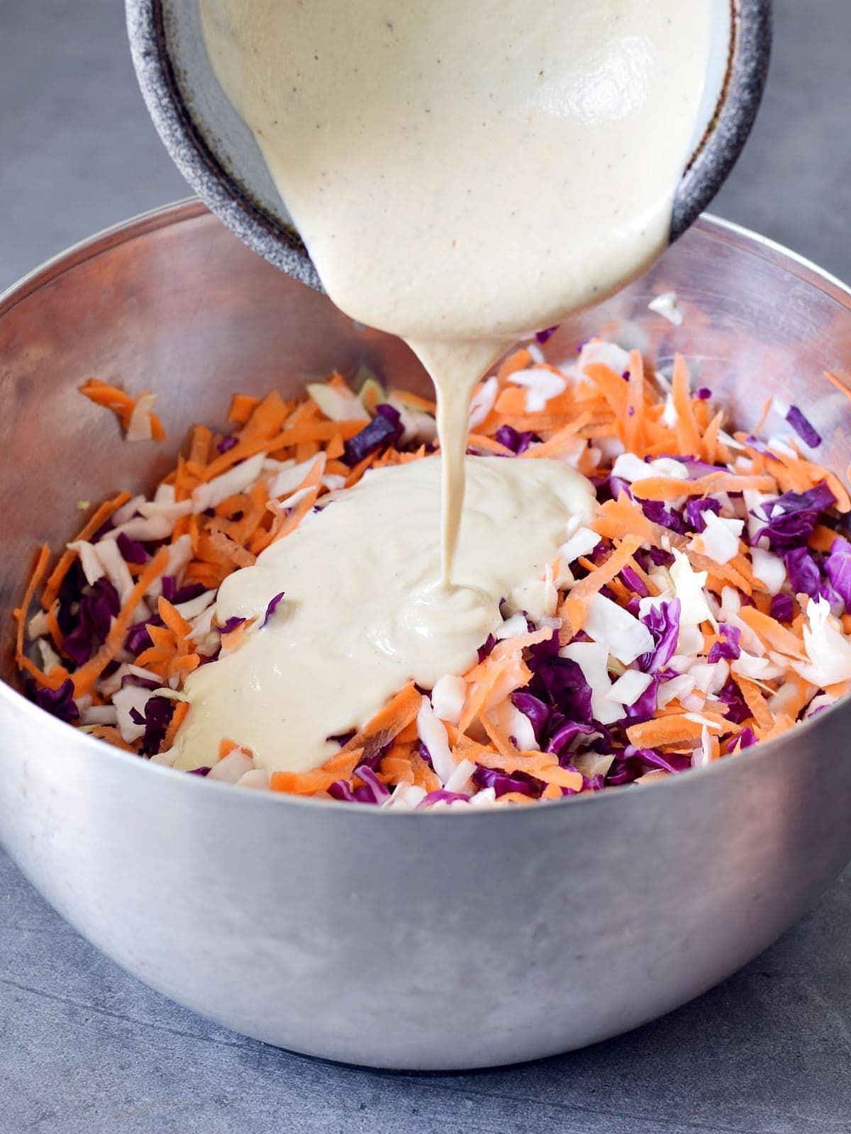 Vegane saure Sahne Dressing wird über Weißkraut, Rotkraut, Karotten und Zwiebel gegossen