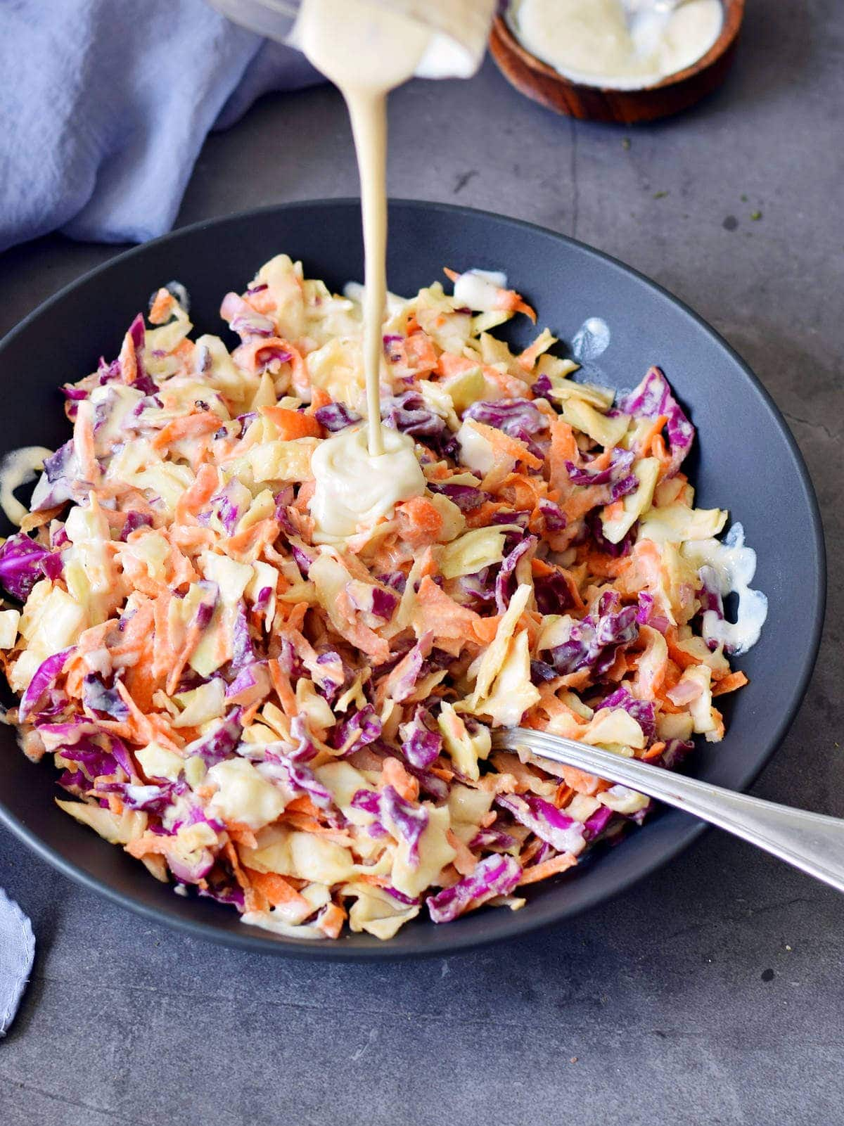 pouring dairy free sour cream over keto coleslaw