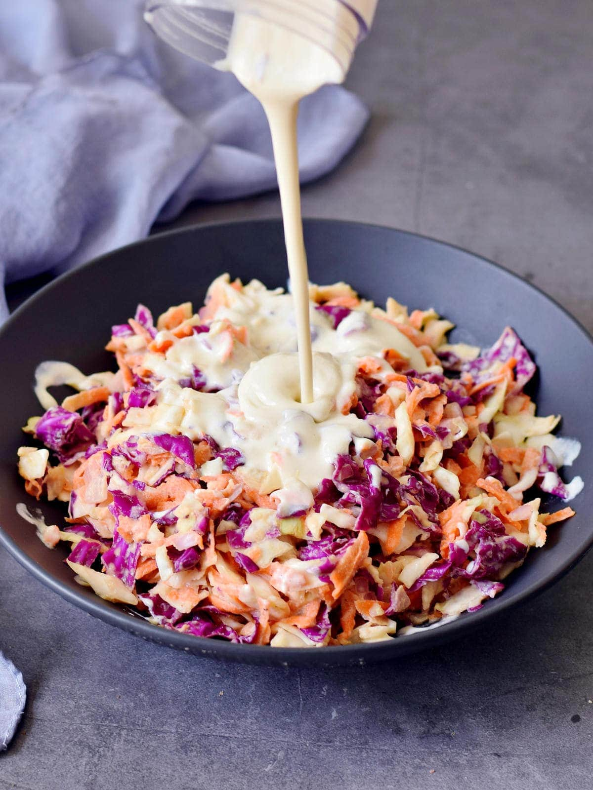 pouring vegan sour cream over keto coleslaw