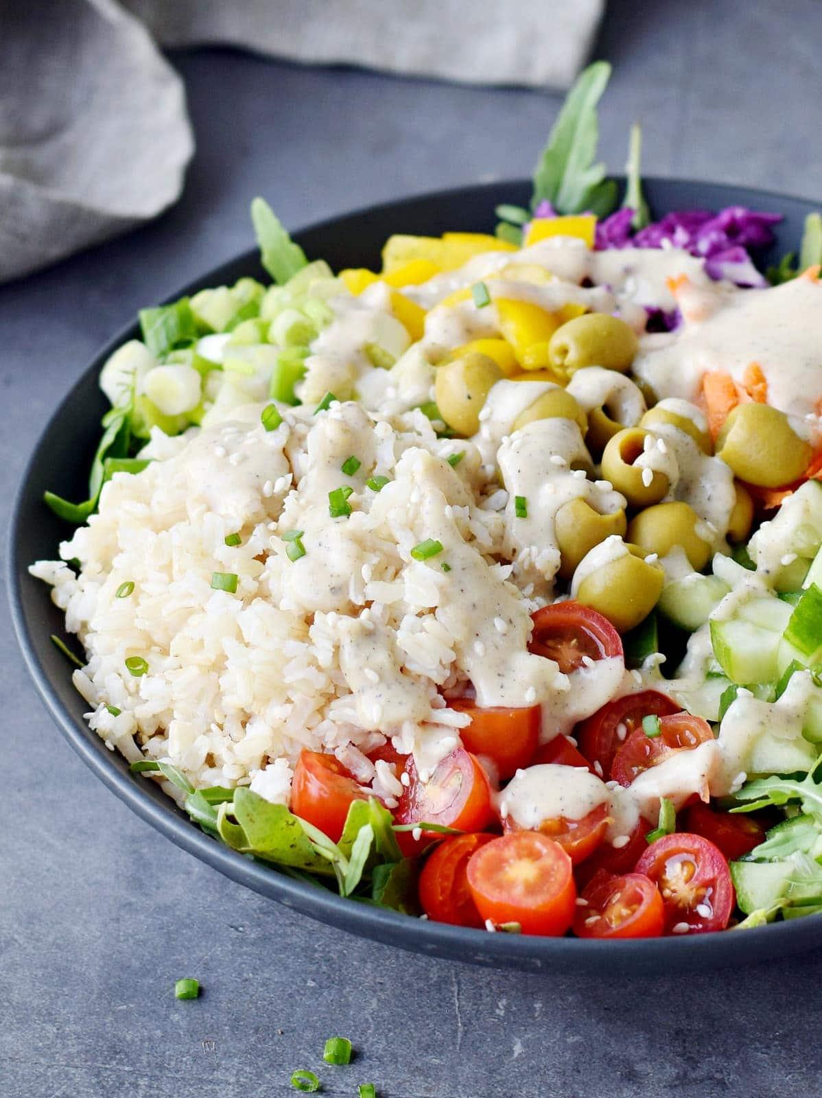 Nahaufnahme einer vegetarischen Salatschüssel mit cremigem Dressing