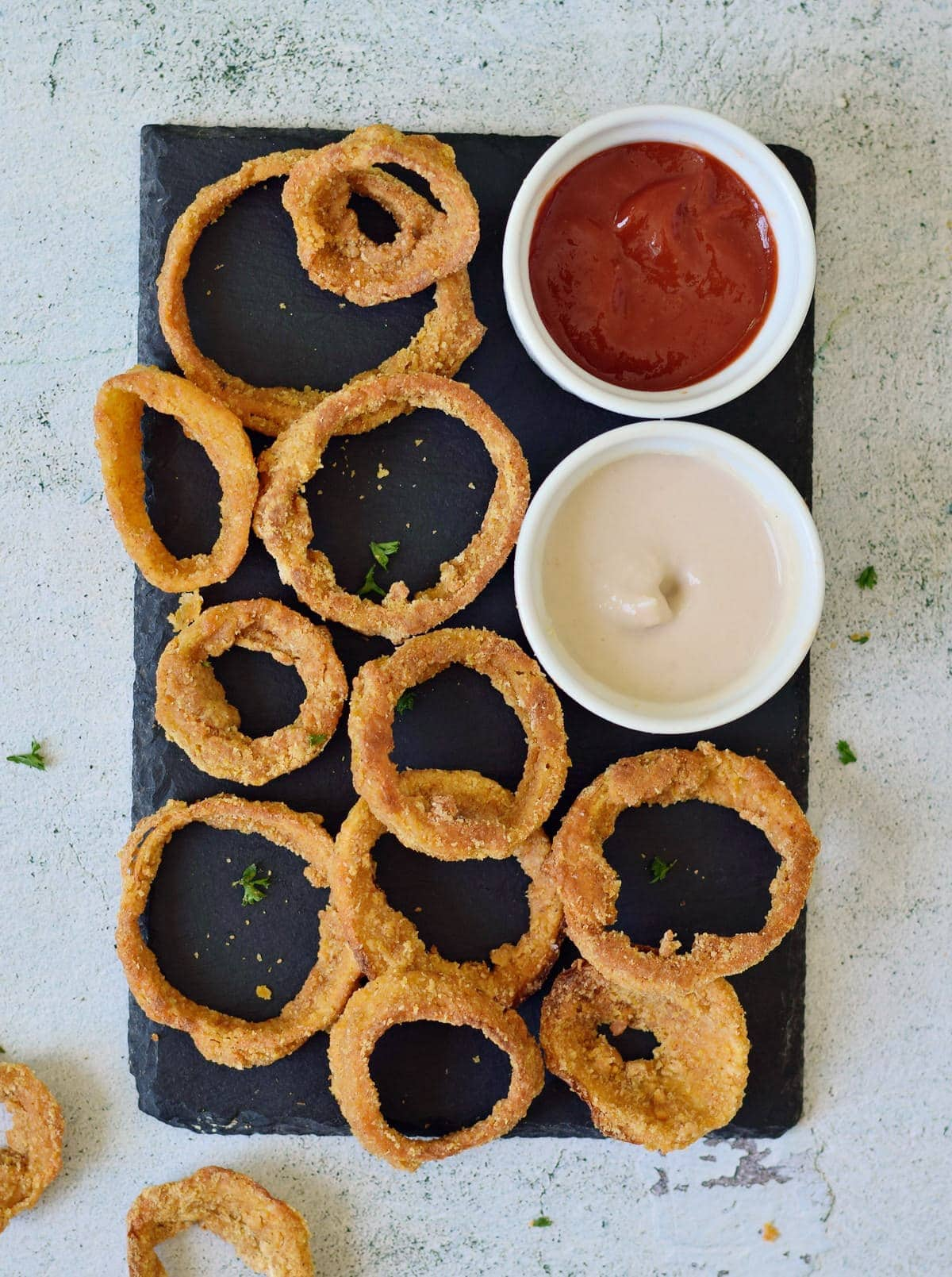 crispy oven baked onion rings on a black board with 2 dips