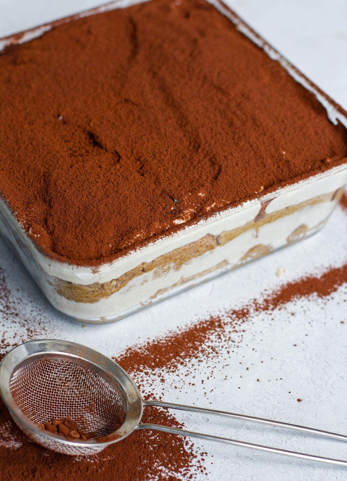Schichtdessert mit Kakaopulver in Aulaufform aus Glas