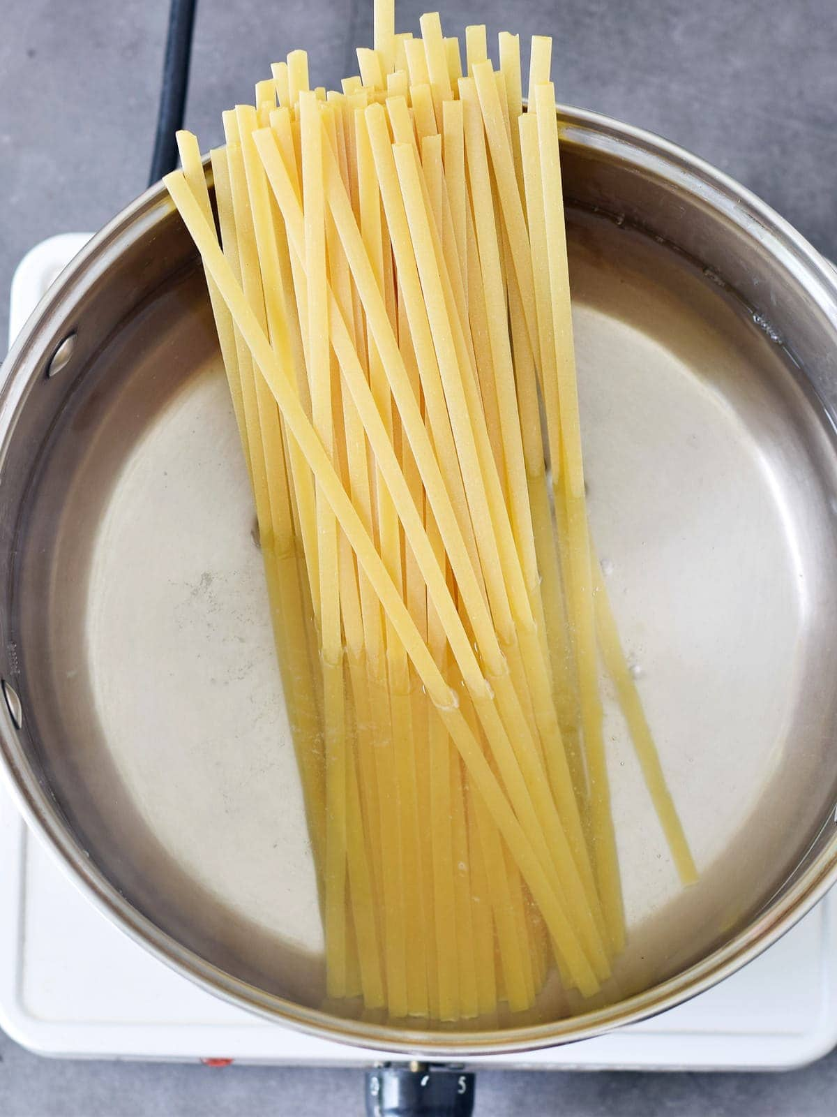 dry fettuccine in a pot with water