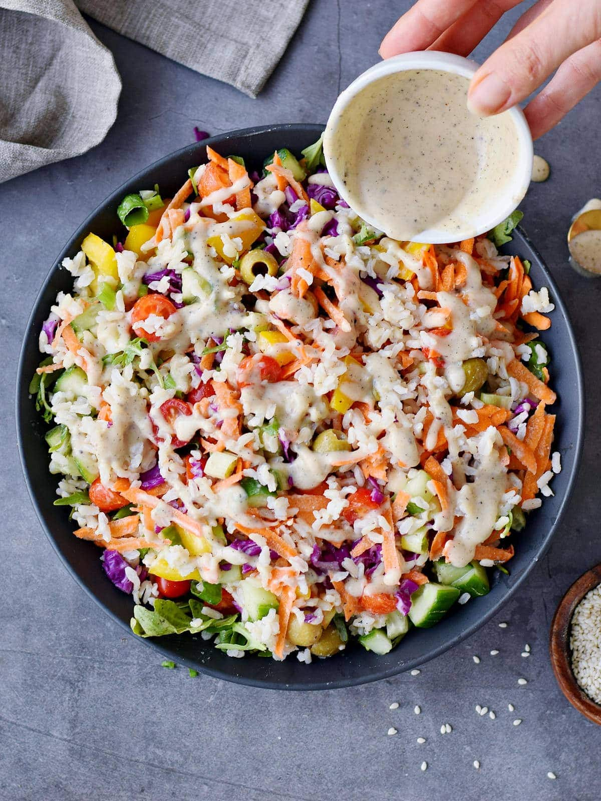 pouring dressing over cold rice salad with veggies in bowl
