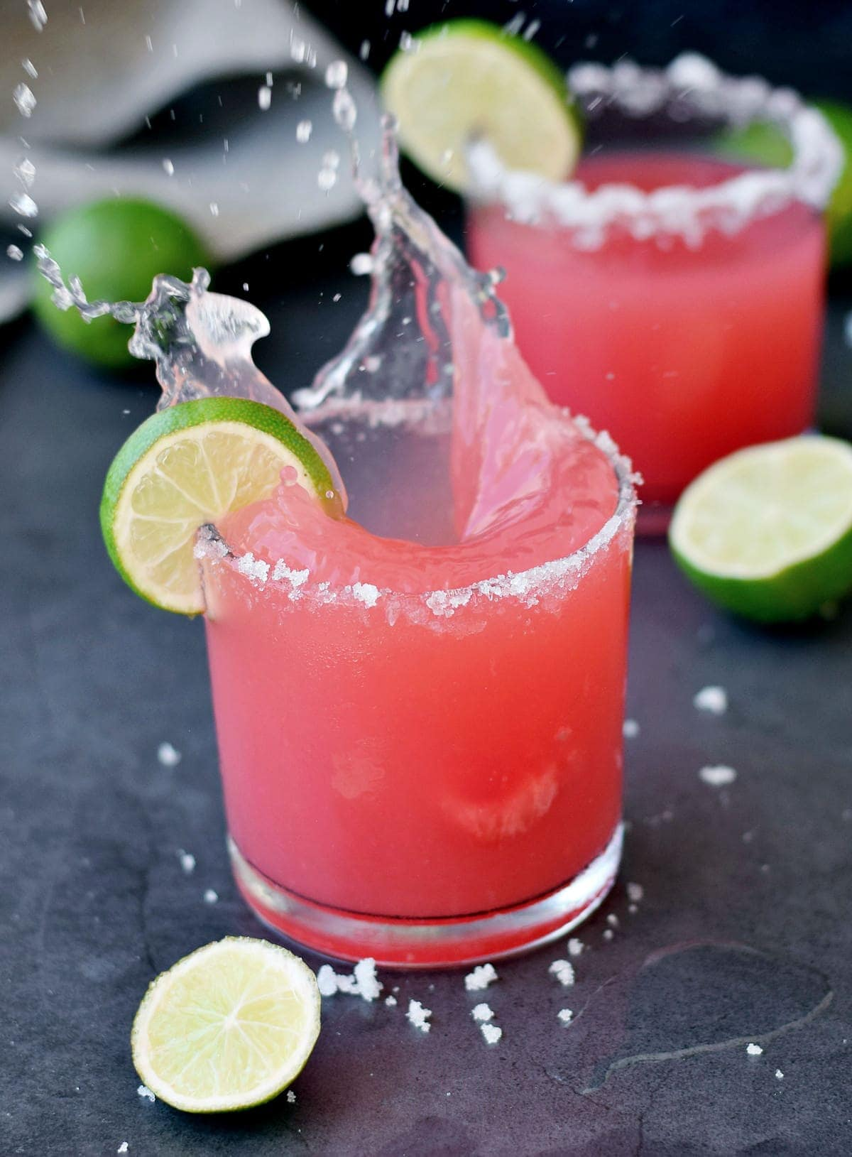 splash shot of watermelon margarita in a glass with lime wedges