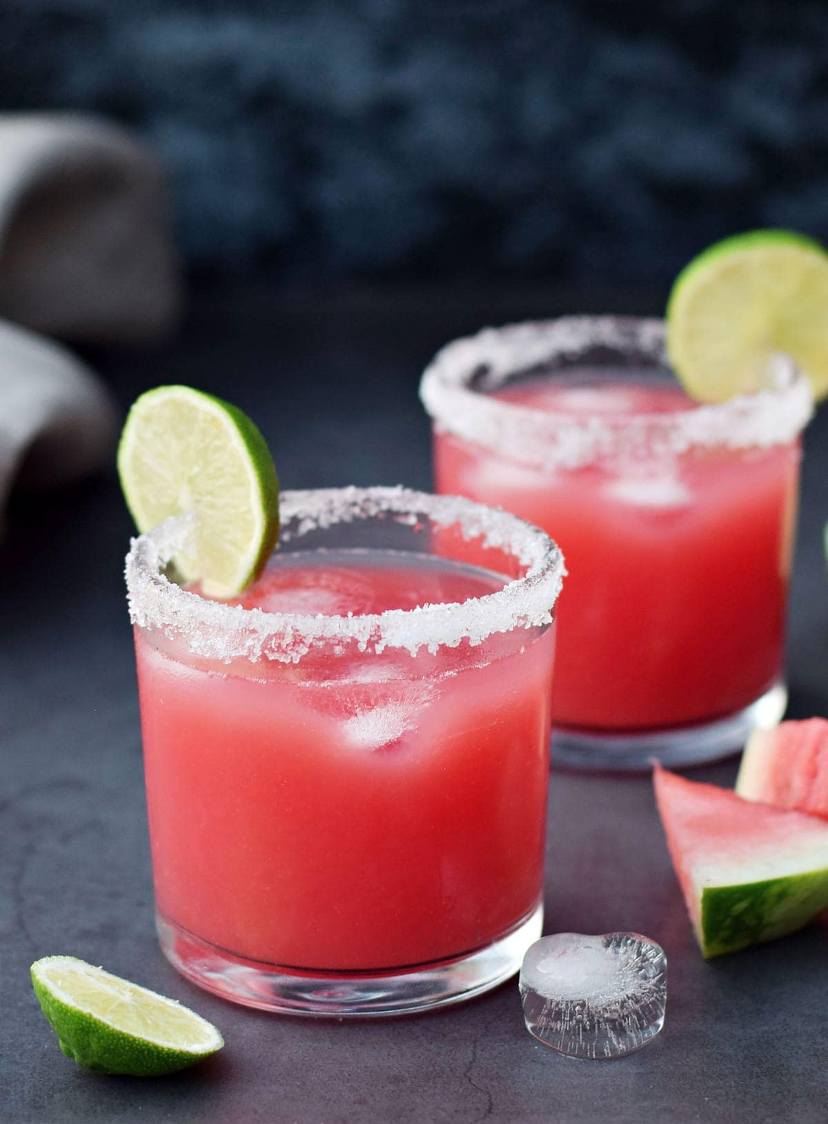 2 glasses of tequila cocktail with watermelons, limes, and salt rim