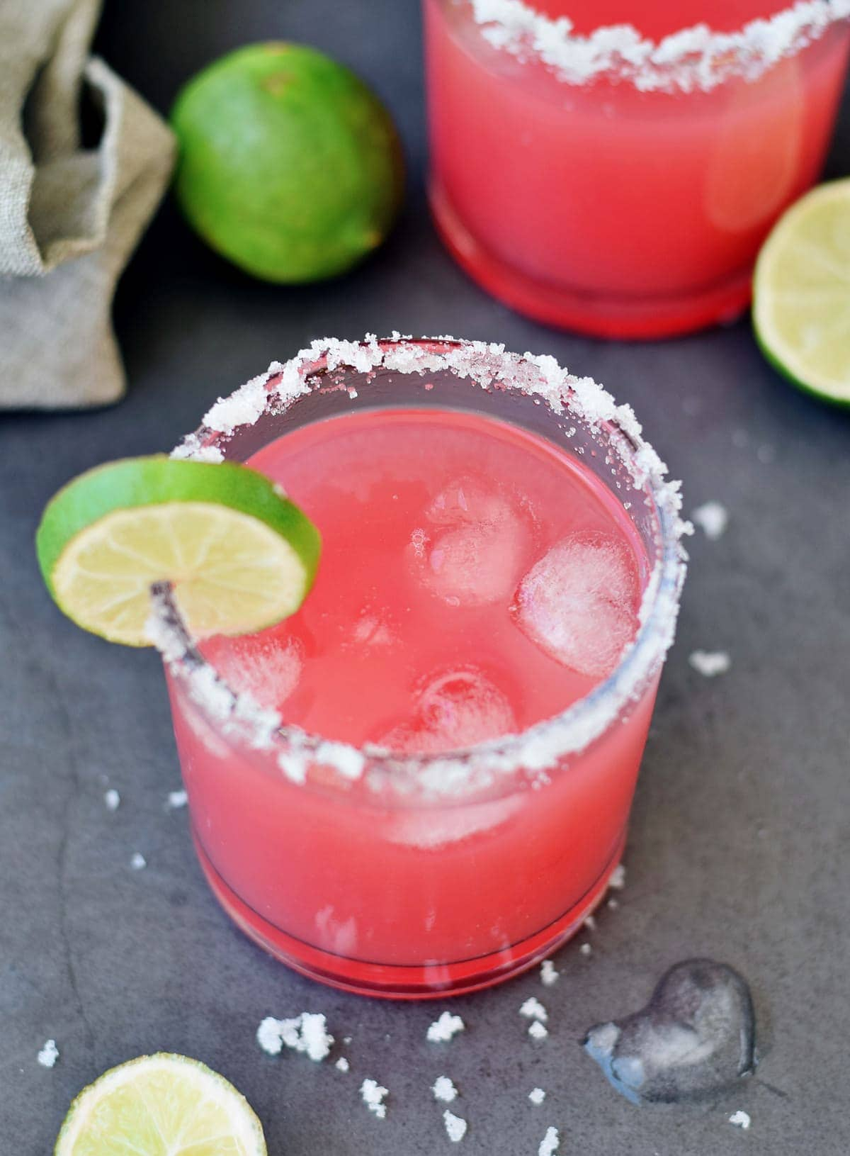 top shot of watermelon cocktail with lime and ice cubes