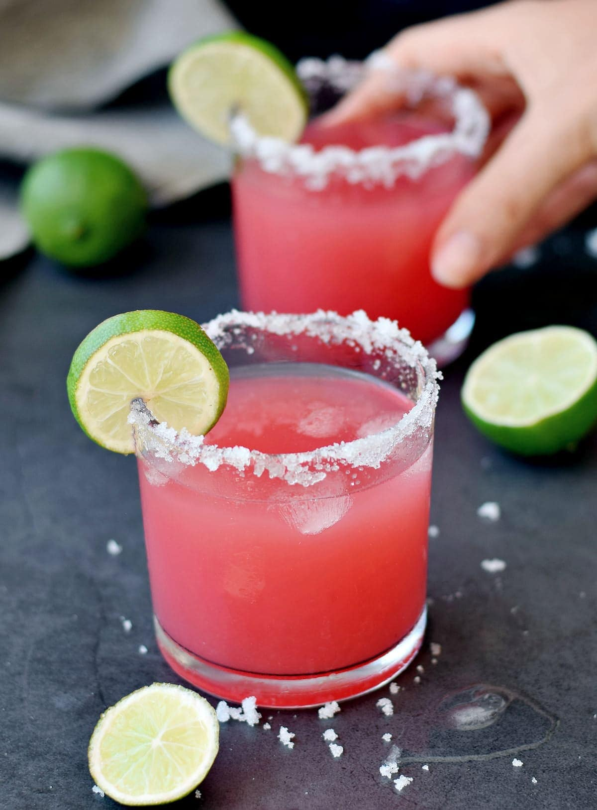 two glasses of pink tequila cocktail with salt rim