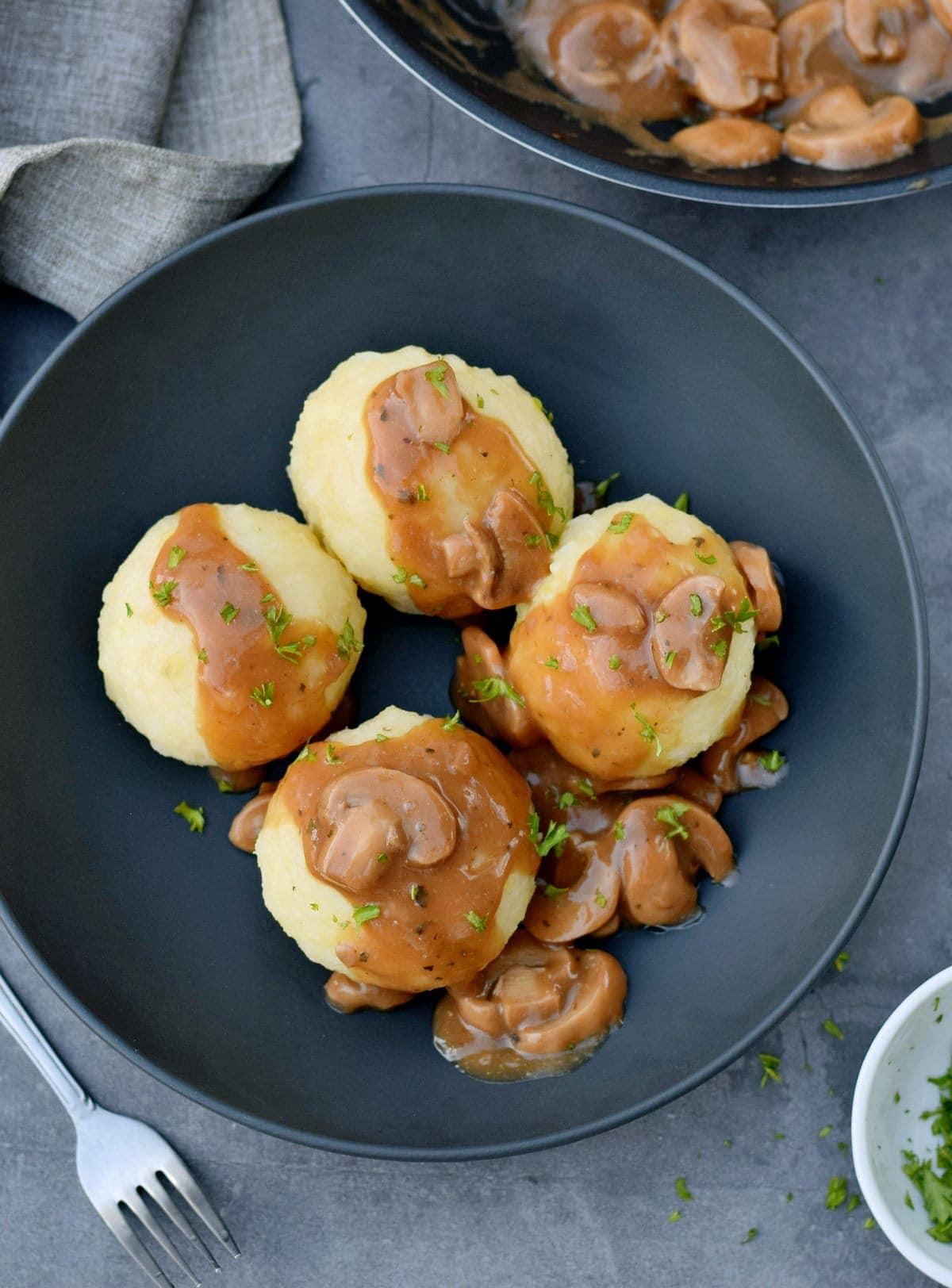 4 Kartoffelknödel mit Pilzsoße in einer schwarzen Schale