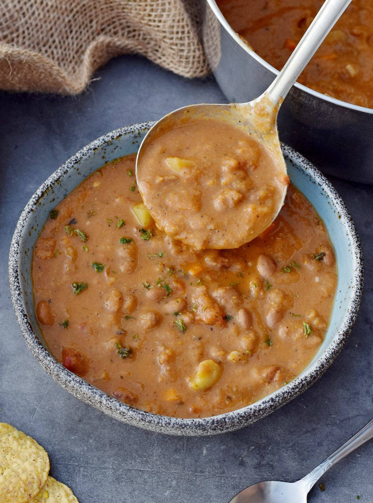 Mexican pinto bean soup in bowl with ladle