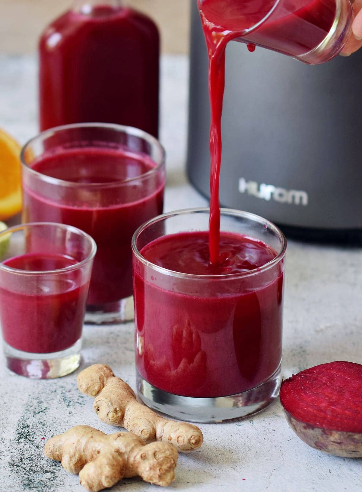 Pouring beetroot immune boosters juice into a glass in front of Hurom juicer