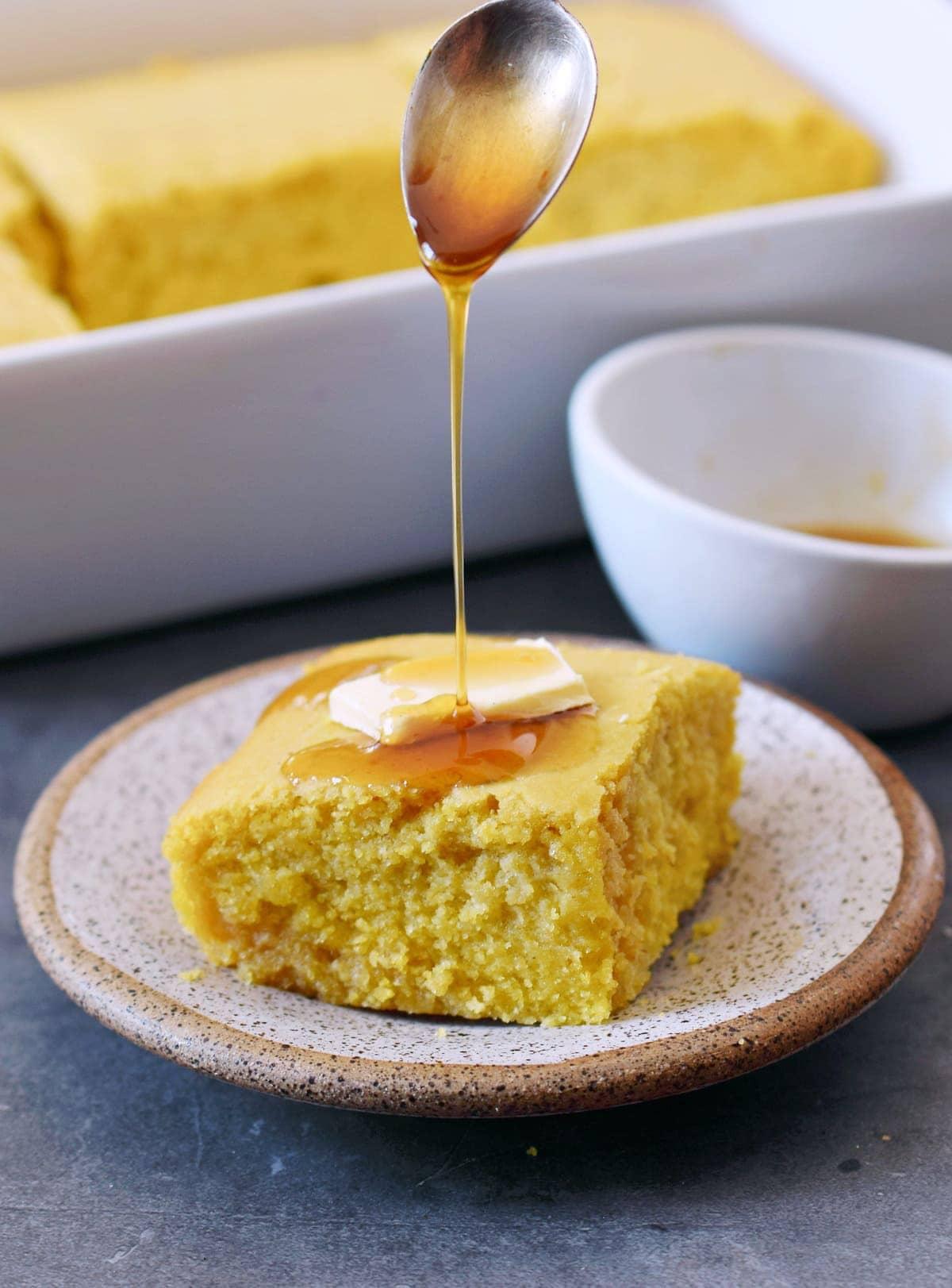 ein Stück Maisbrot mit veganer Butter und Ahornsirup auf Teller