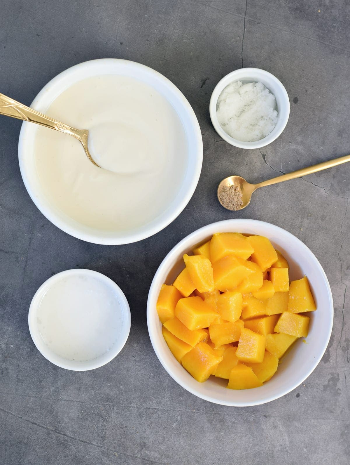 chopped mangoes, yogurt, plant-based milk, sugar, and cardamom on back backdrop