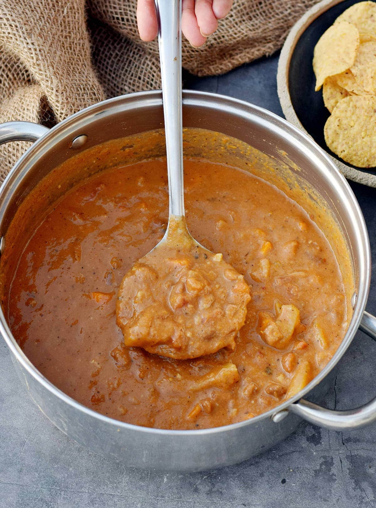 hearty Mexican pinto bean soup in large pot with ladle