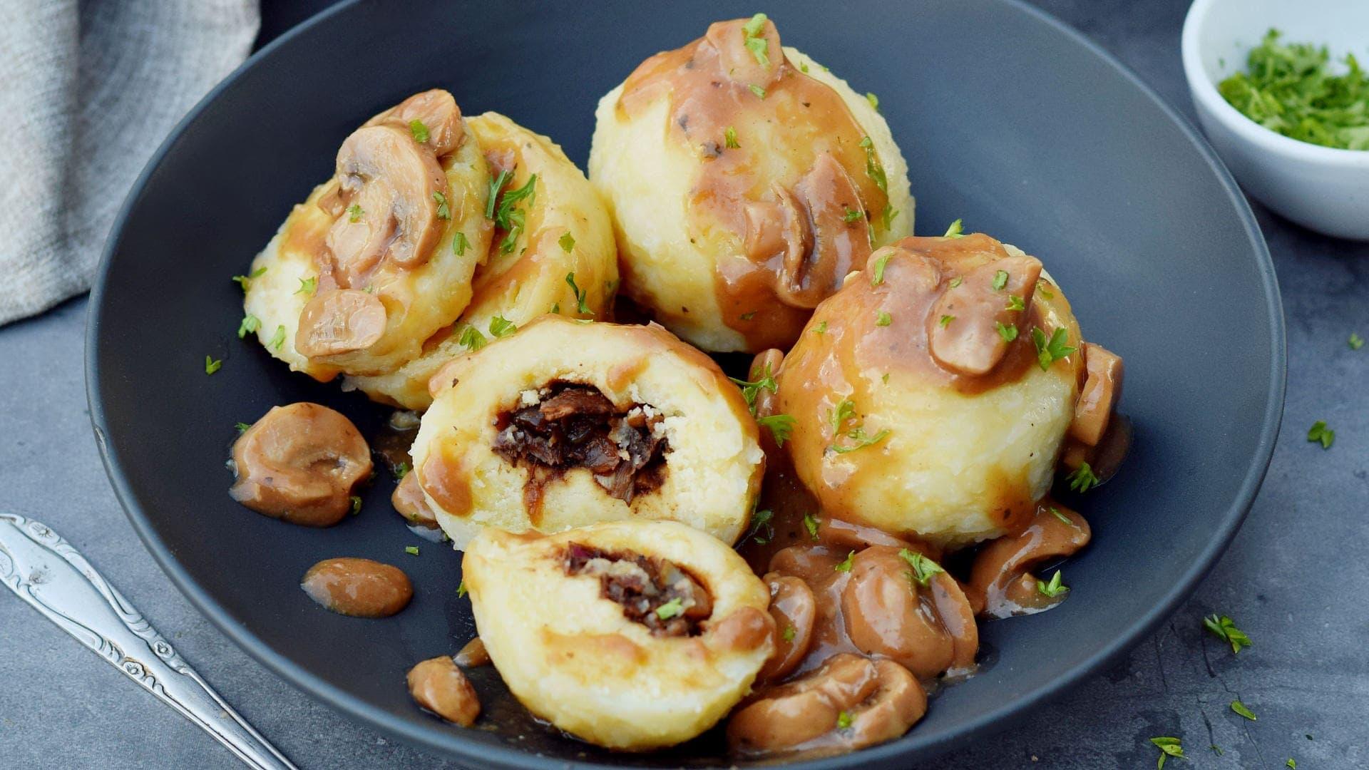 horizontal photo of stuffed potato dumplings with mushroom gravy
