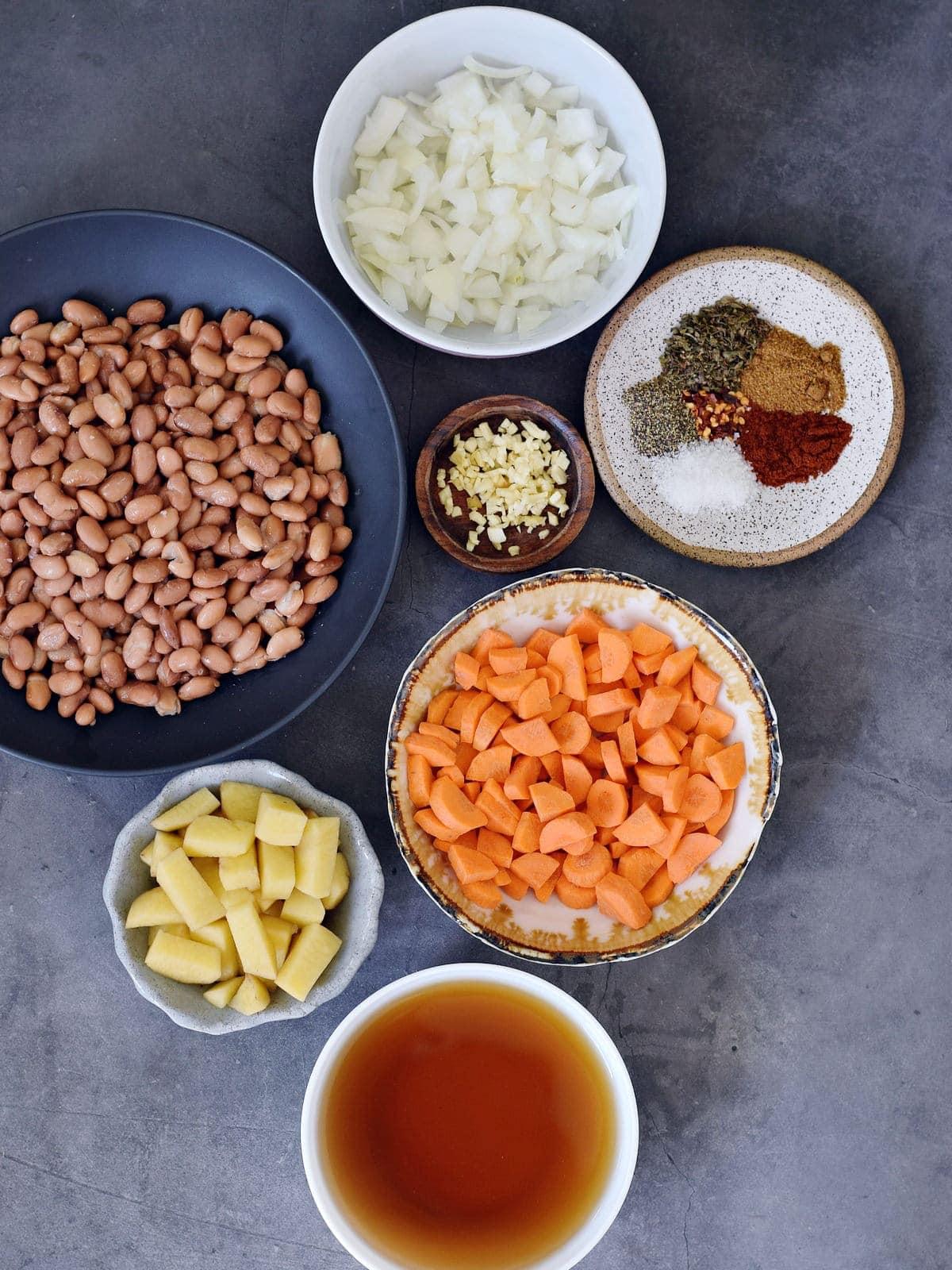 Pintobohnen, Zwiebeln, Knoblauch, Karotten, Kartoffeln, Brühe und Gewürze auf grauem Hintergrund