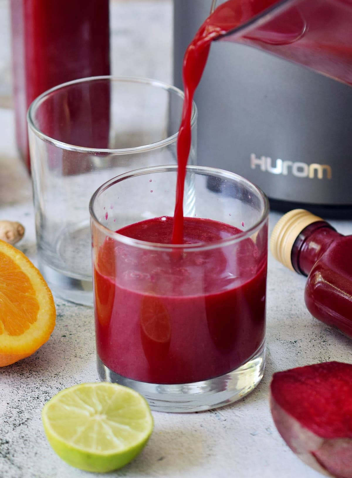 pouring beetroot juice into glass in front of Hurom juicer