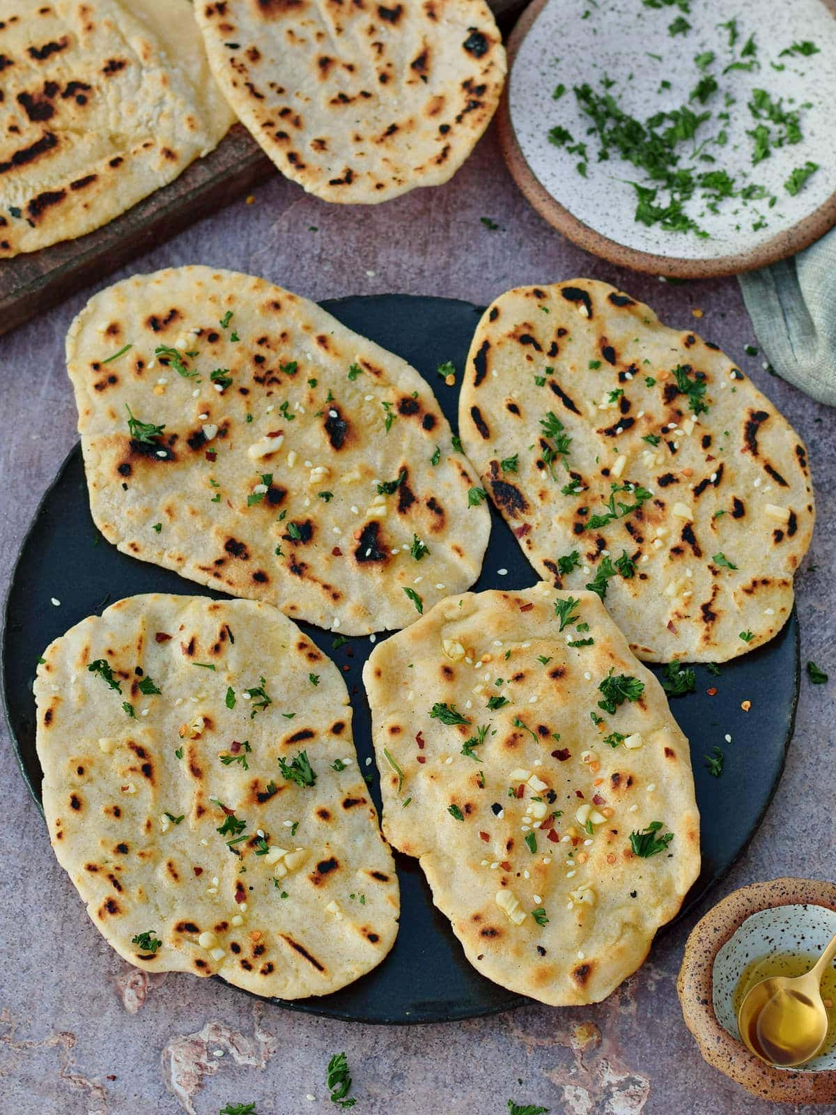 4 pieces of vegan gluten-free naan on black plate with herbs and garlic
