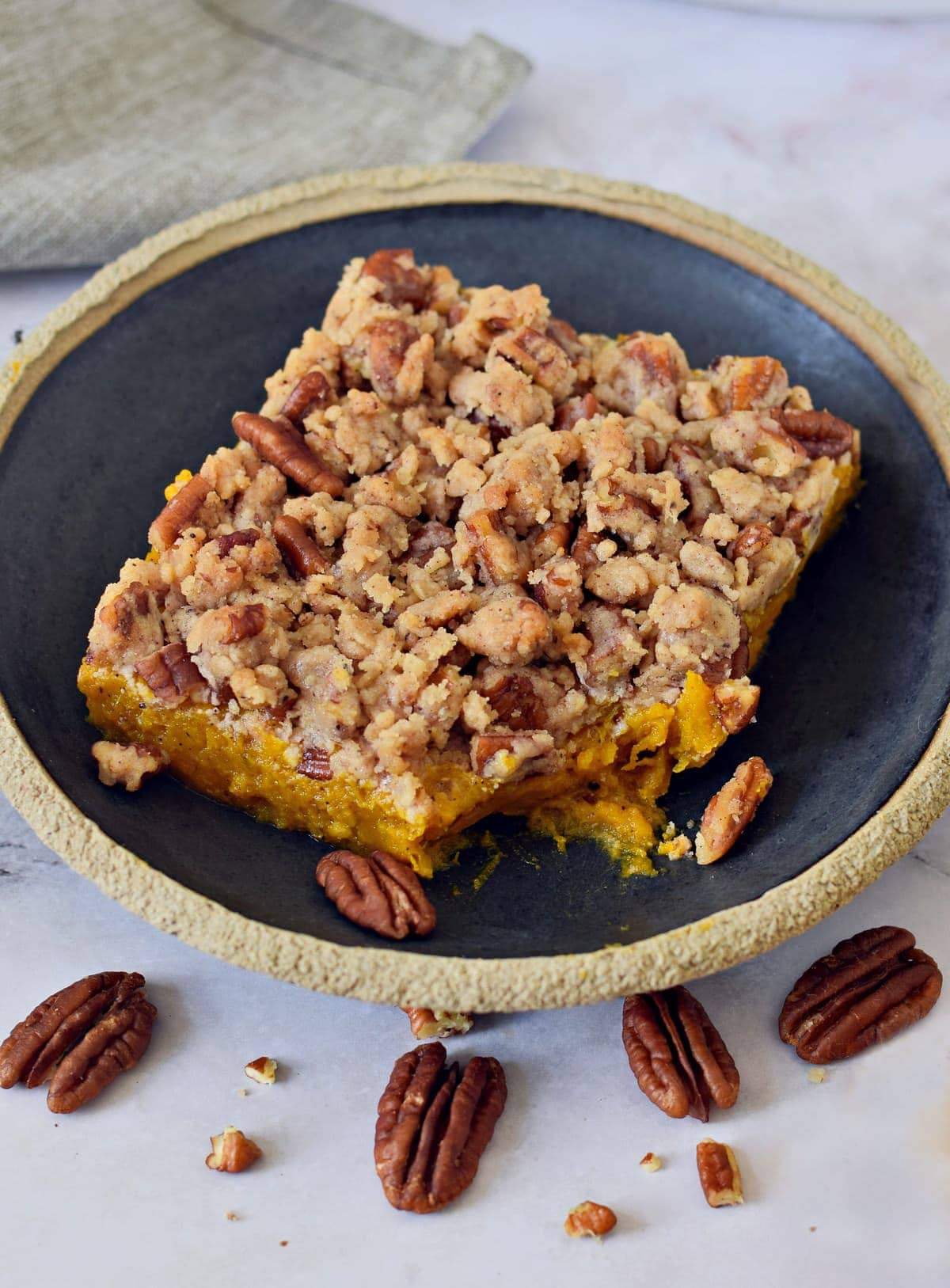 A piece of a healthy bake with streusel pecan topping on black plate
