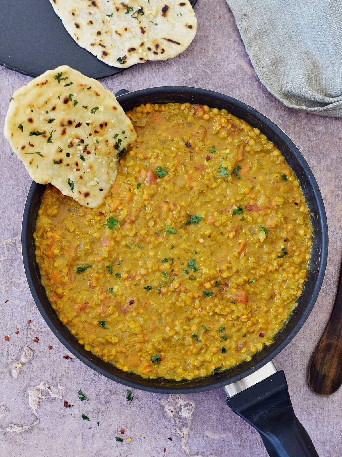 A piece of gluten-free Indian flatbread submerged in red lentil dahl in black skillet