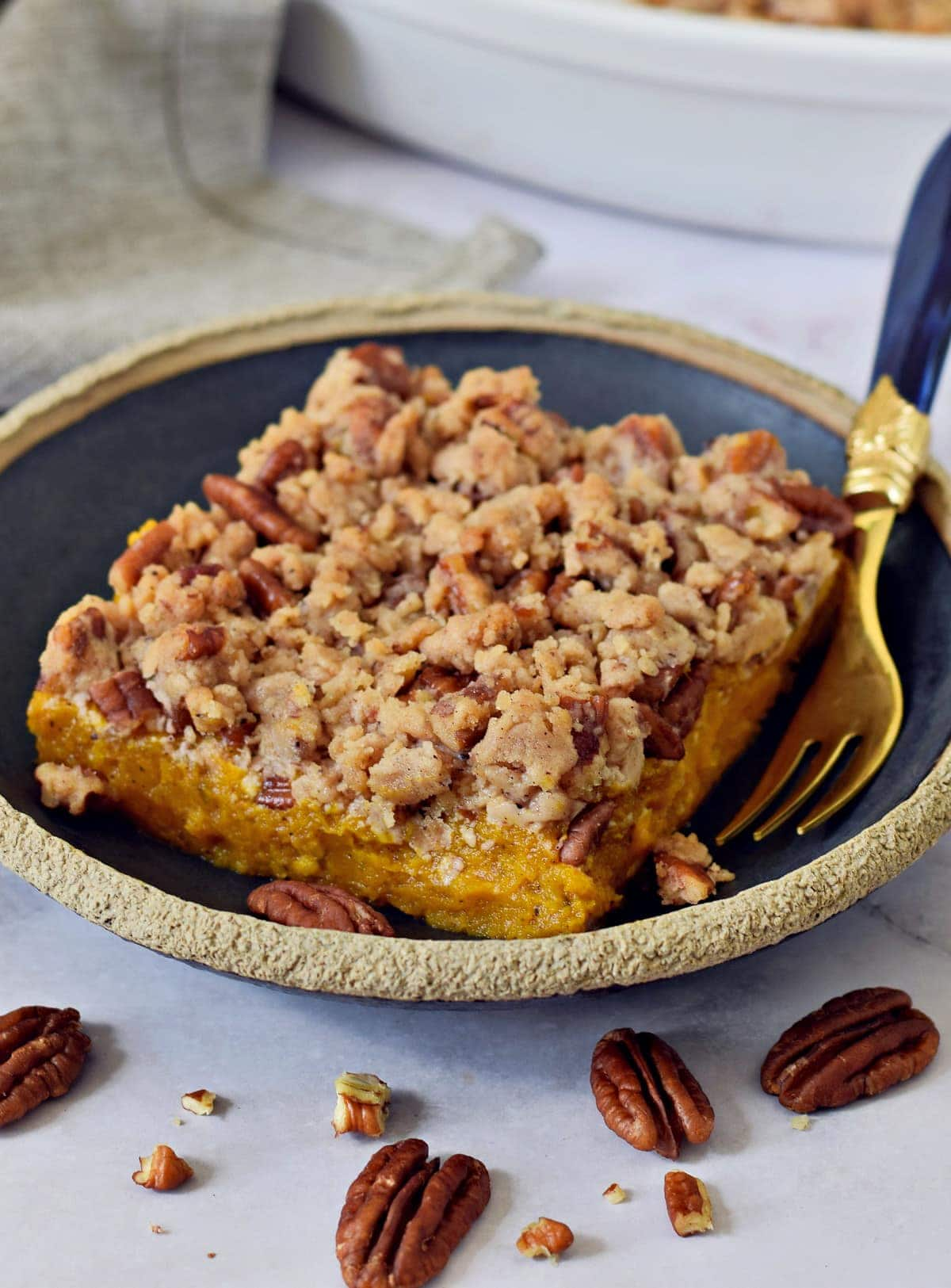 A piece of vegan sweet potato casserole with crumble pecan topping on black plate with fork