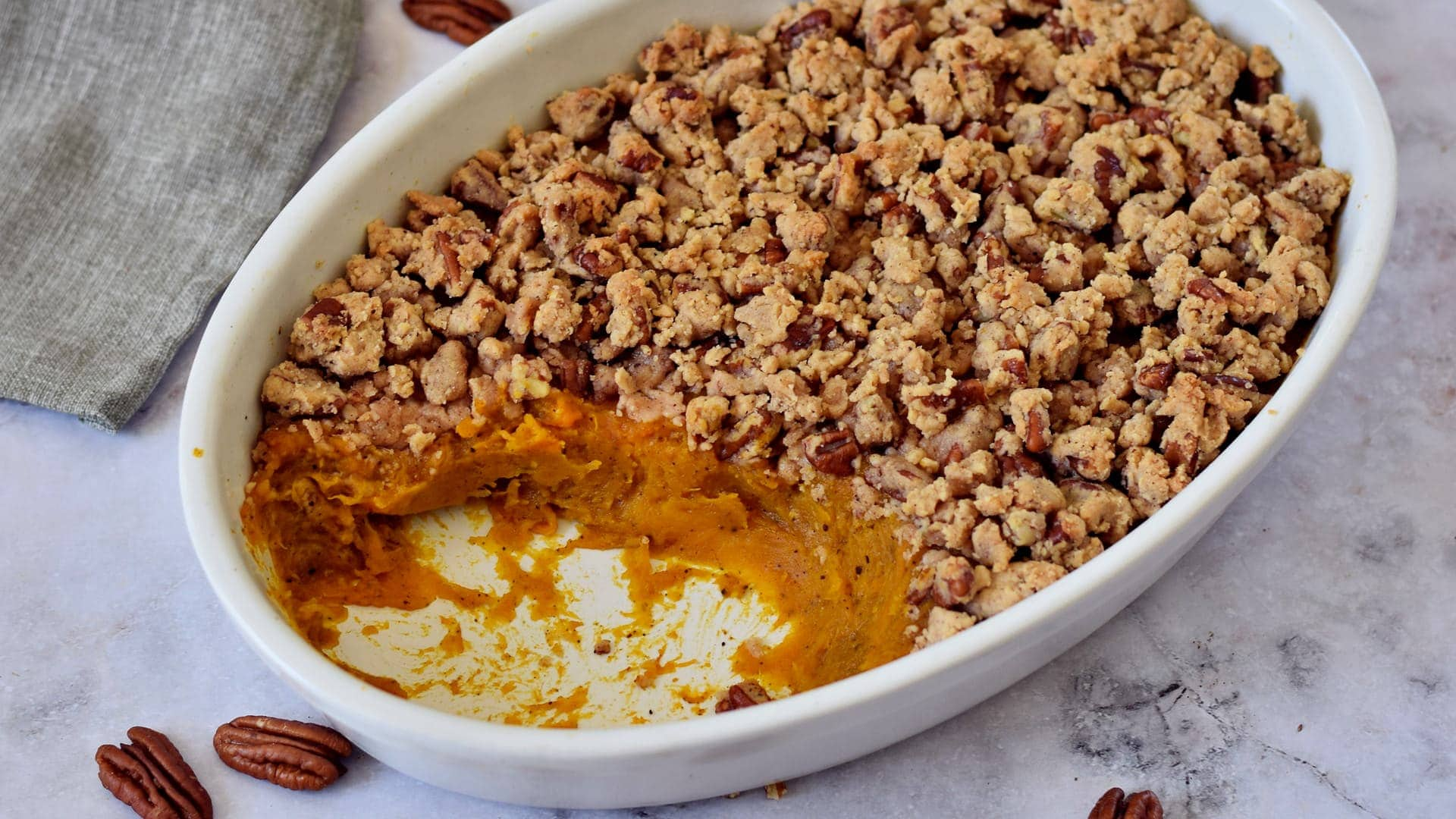Horizontal photo of a bake with sweet potatoes and pecan streusel topping