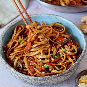 eating vegetable stir fry noodles with chopsticks