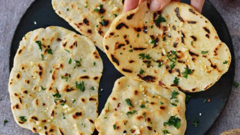 gluten-free naan bread on a plate with hand pinching one