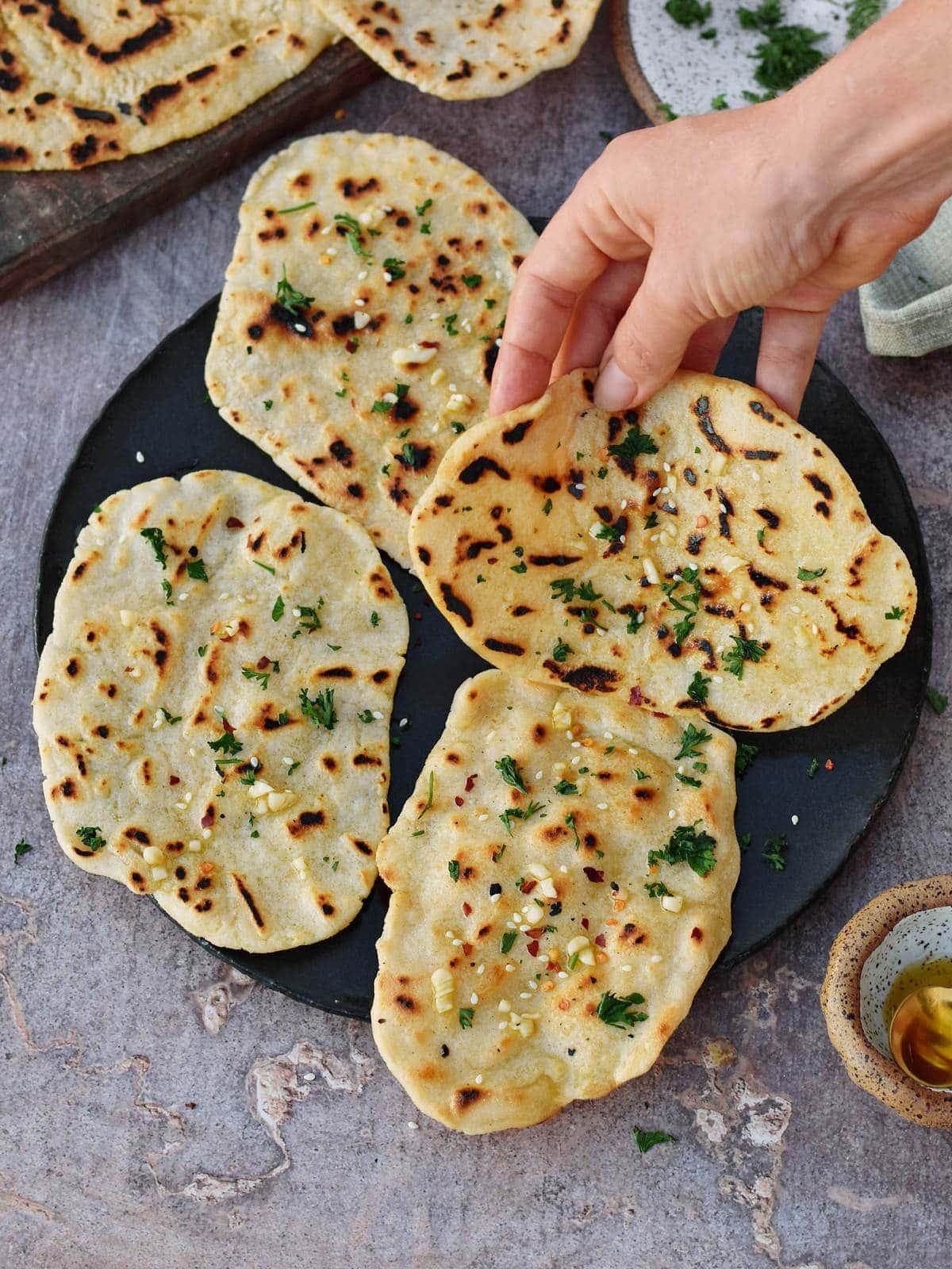 Naan Brot auf einem Teller mit einer Hand die danach greift